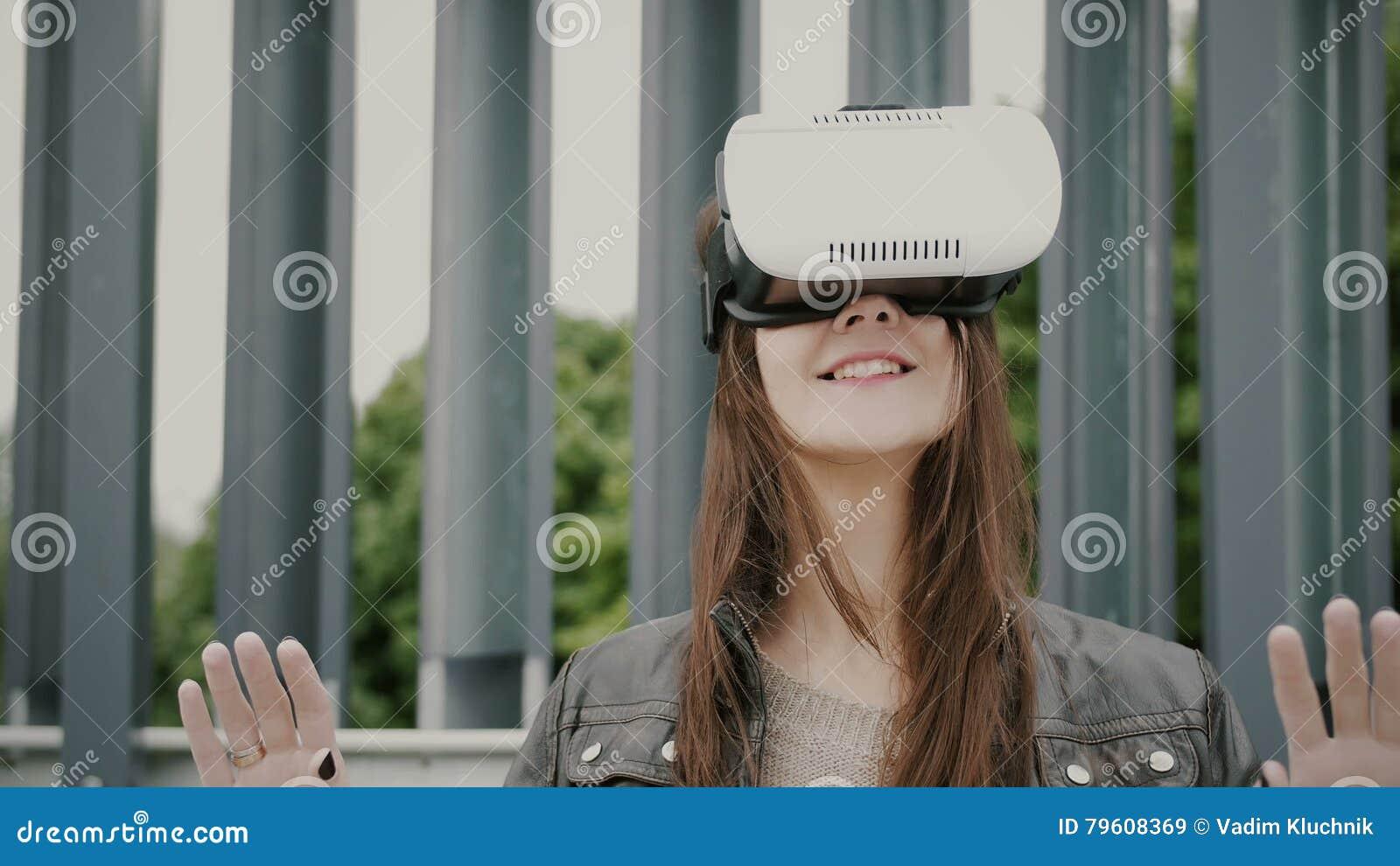 A menina moreno da mulher com cabelo de ondulação usa vidros da realidade virtual no espaço urbano 4K