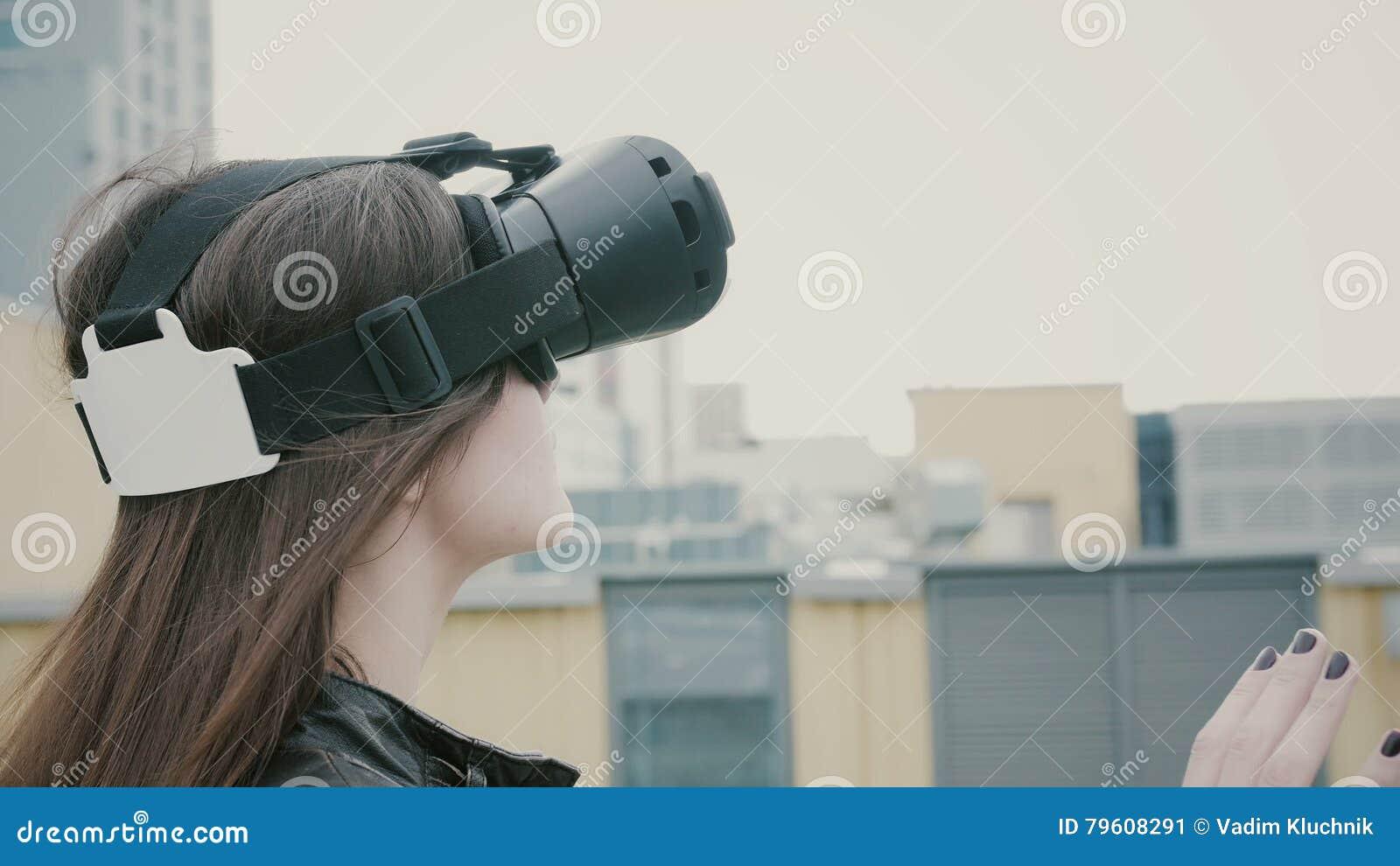 A menina moreno da mulher com cabelo de ondulação usa vidros de uma realidade virtual no telhado 4K