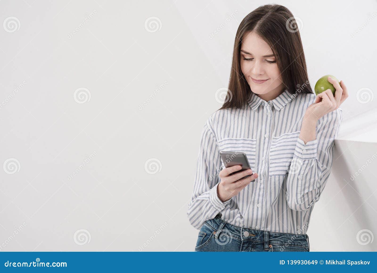 Menina moreno delgada com cabelo longo em um fundo branco perto da janela do escritório Usa um smartphone e a conversa e