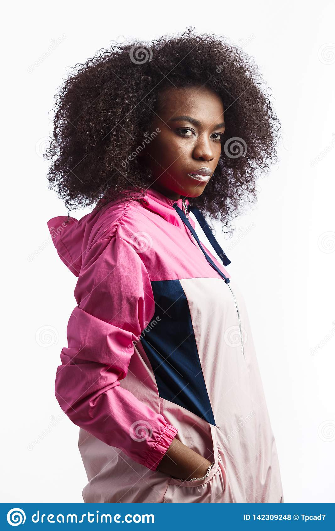 A menina moreno encaracolado nova picante vestida no revestimento de esporte cor-de-rosa está no fundo branco no estúdio