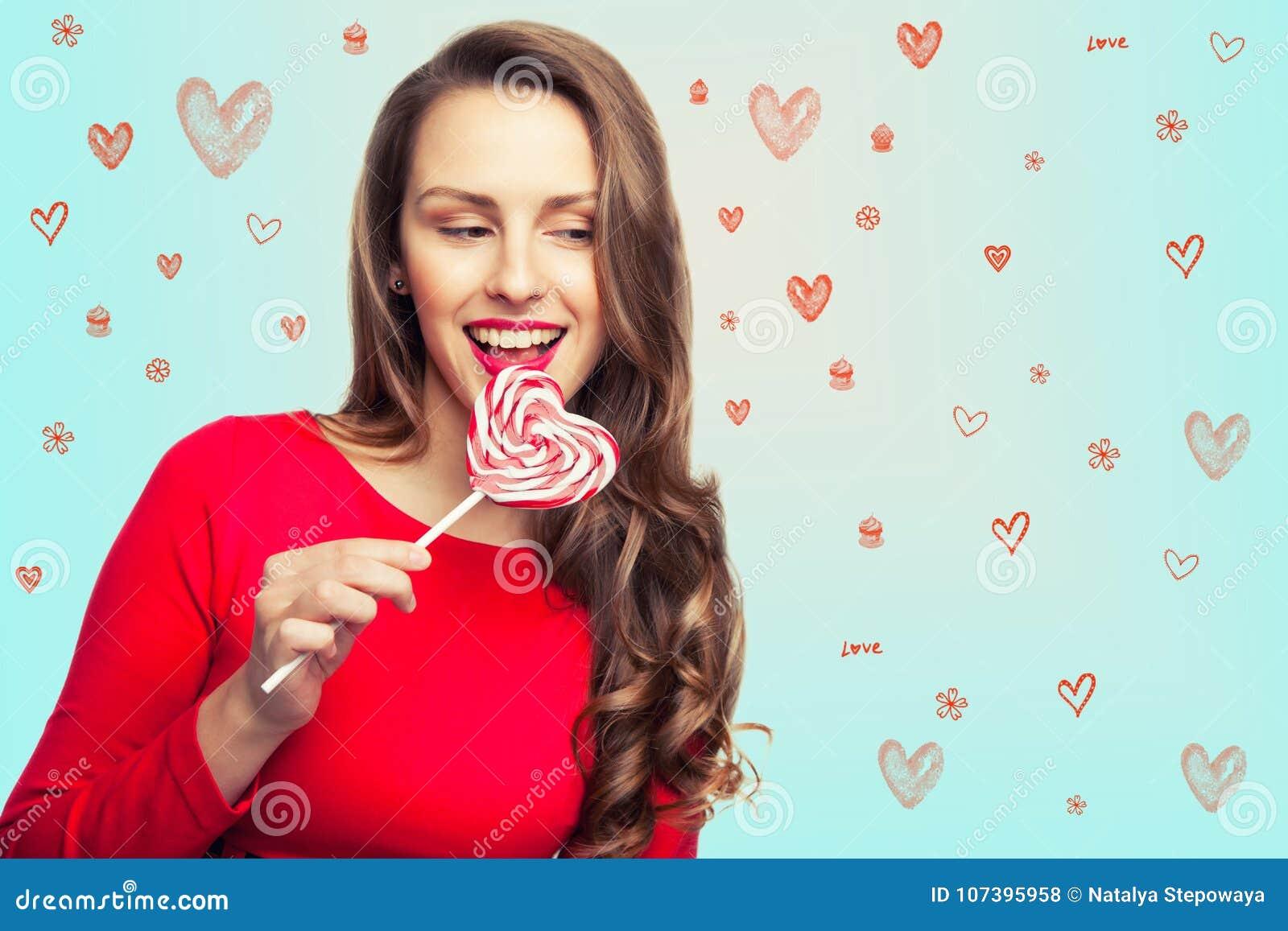 A menina moreno está guardando um pirulito como um coração e um riso para o dia do ` s do Valentim
