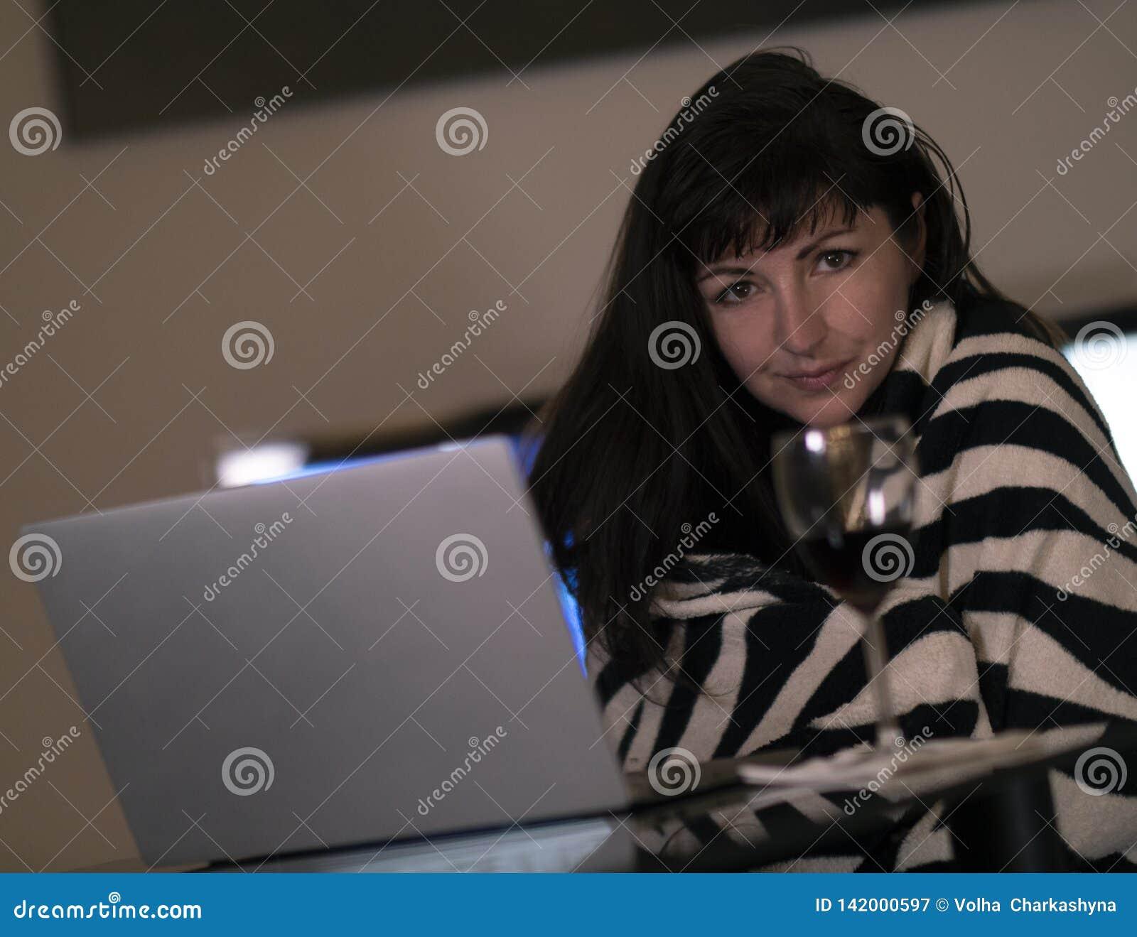 A menina moreno está sentando-se no em casa atrás de um portátil, está sorrindo-se e está olhando-se a câmera com um vidro do vin