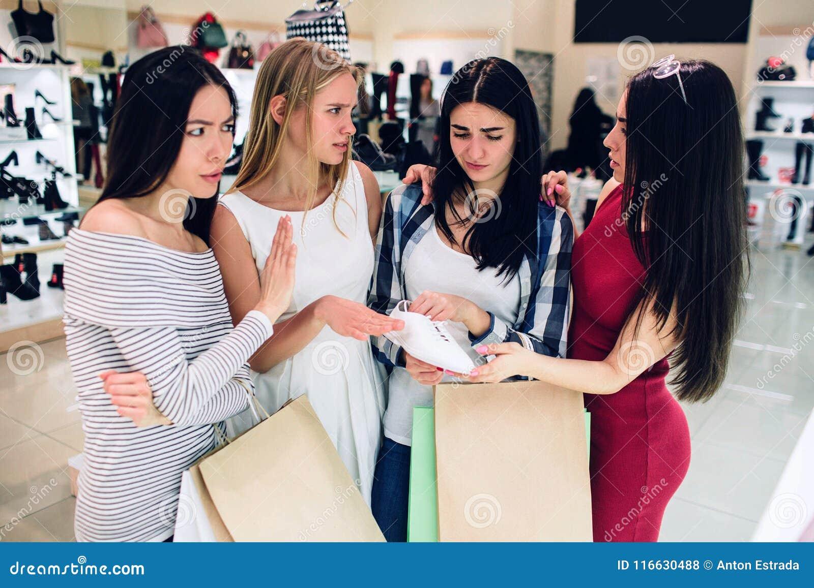 A menina moreno na camisa está guardando uma das cruzes brancas Duvida para comprá-lo Seu amigo está dando recomenda-lhe