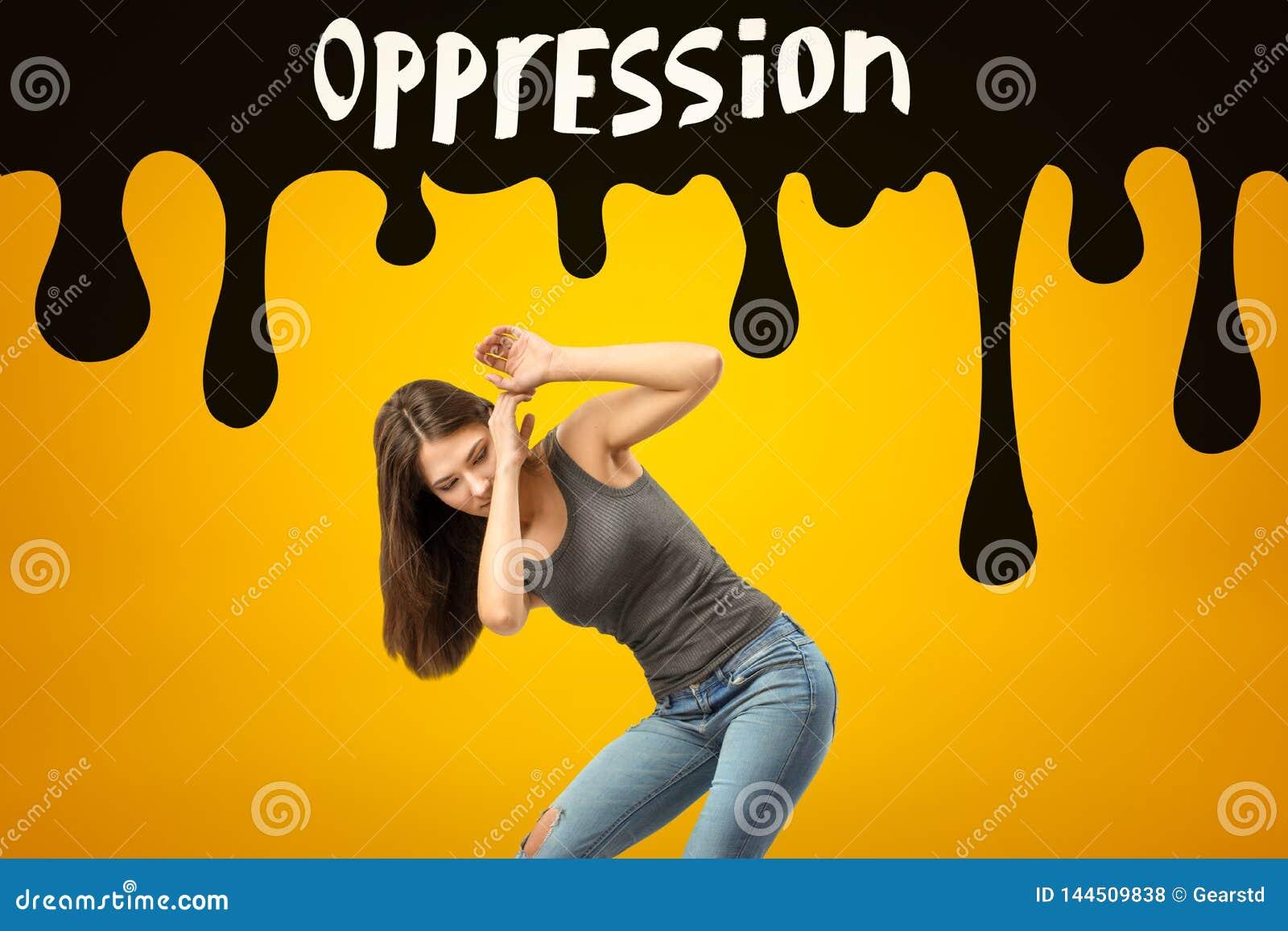 Menina moreno nova que veste calças de brim ocasionais e o t-shirt que protegem-se com mãos do sinal preto da OPRESSÃO no amarelo