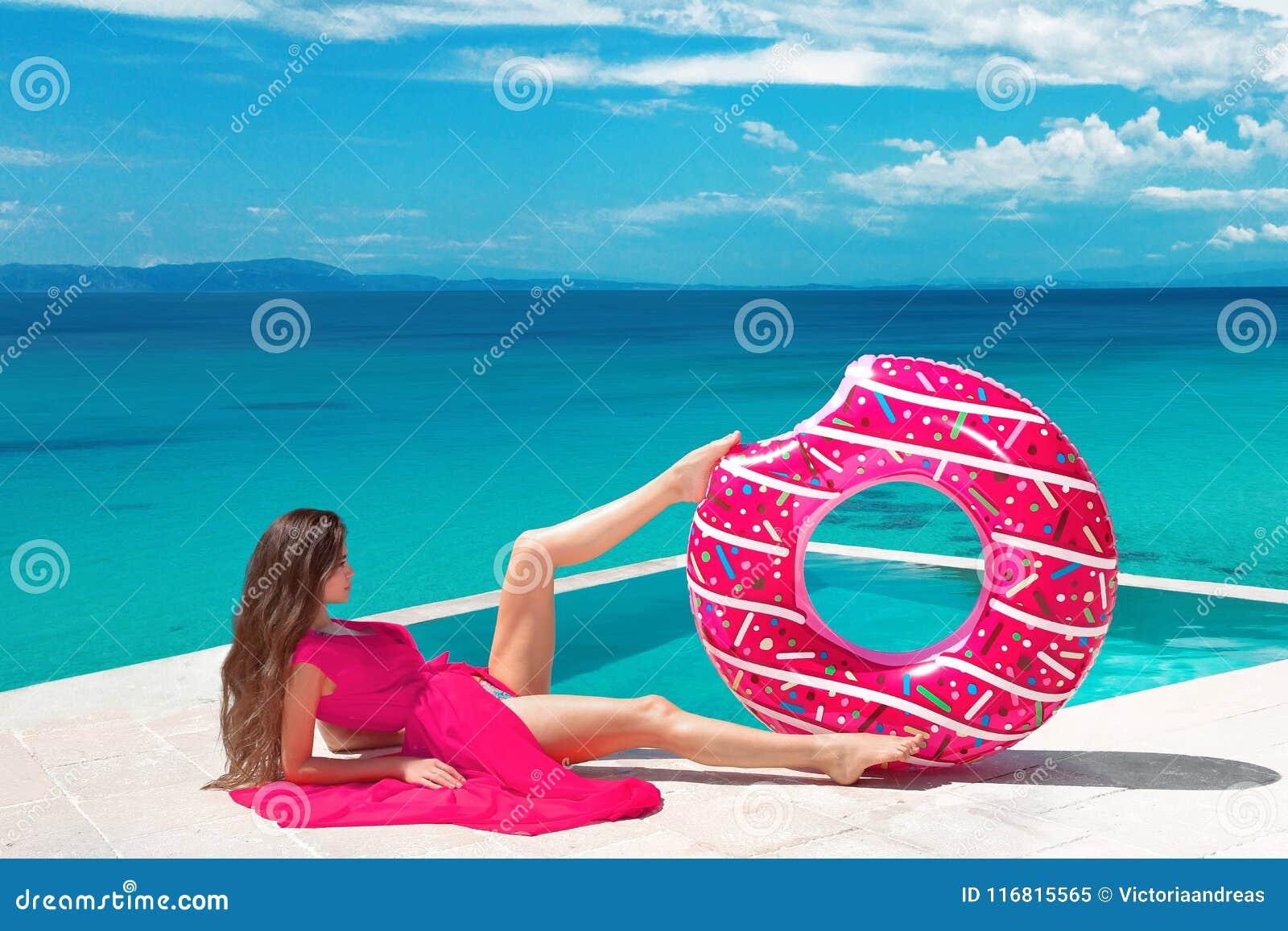 Menina moreno  sexy  que relaxa com anel inflável do flutuador pelo ho