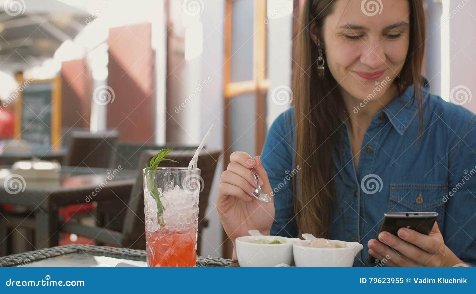 A menina moreno usa o telefone esperto ao sentar-se fora em um café, comendo o gelado 4k,