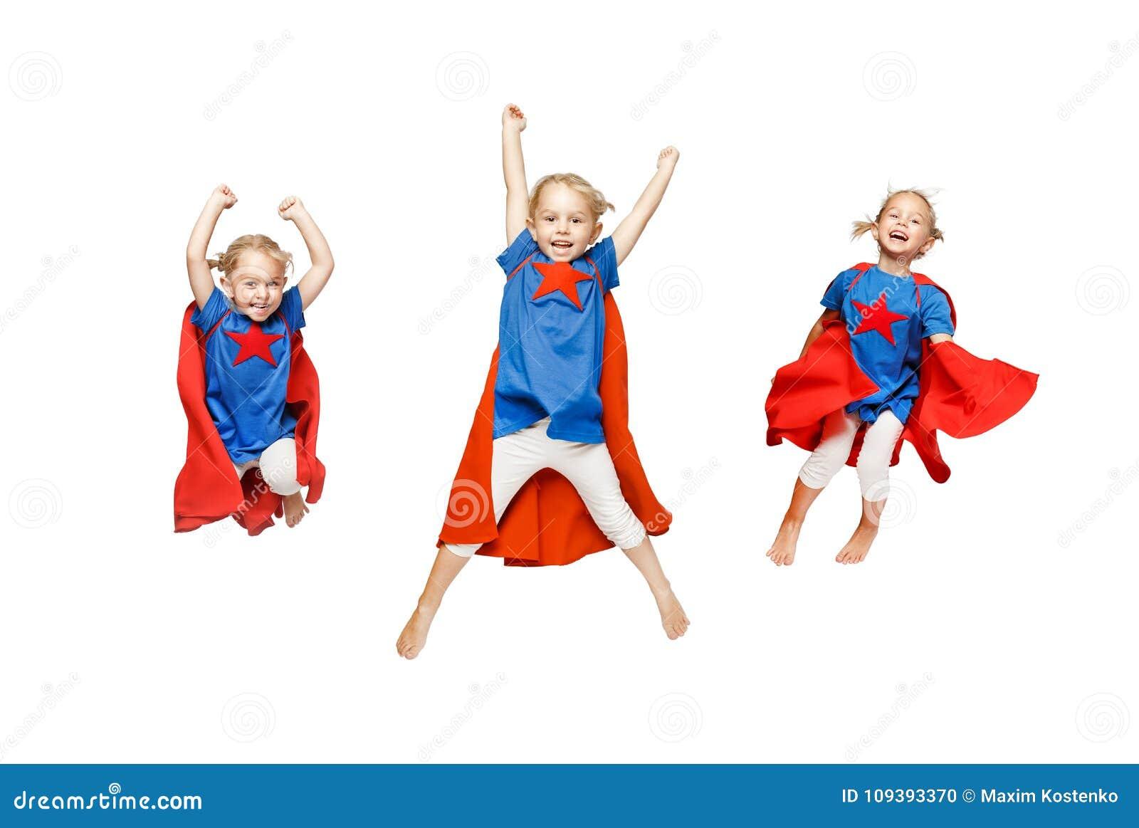 A menina muito entusiasmado vestiu-se como o salto do herói isolada no fundo branco