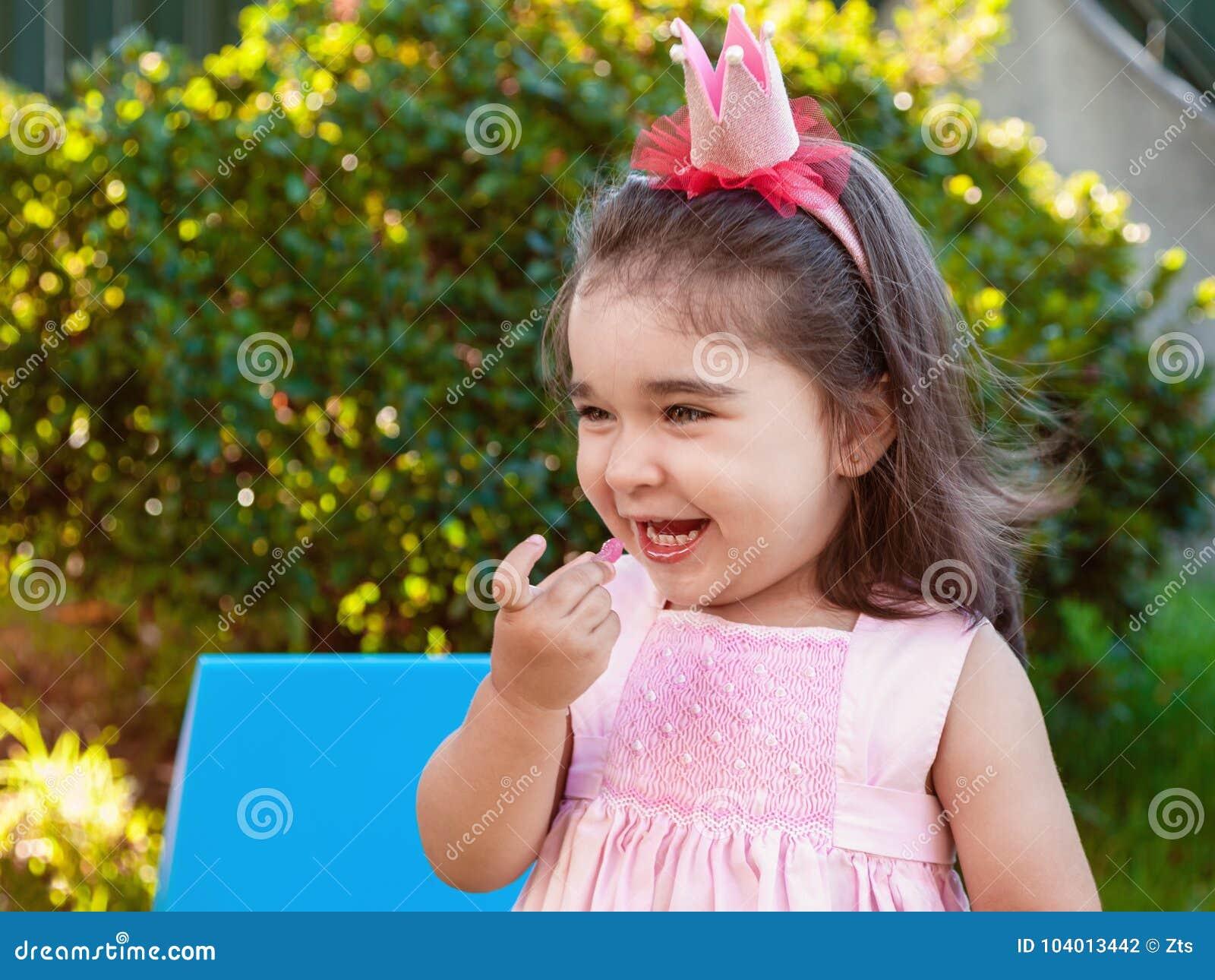 Menina muito feliz da criança do bebê, comendo gummies rindo e sorrindo no partido exterior vestido no vestido cor-de-rosa