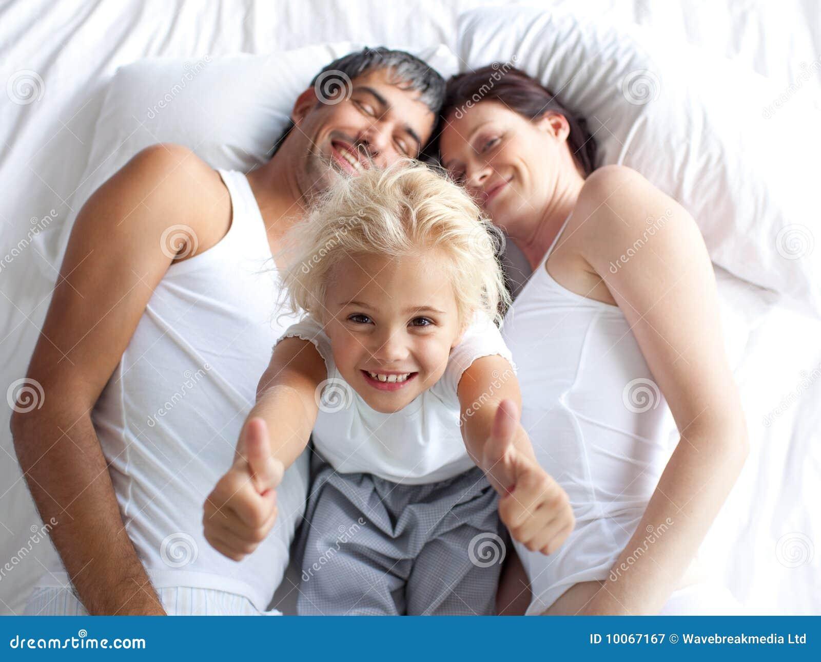 A menina na cama com polegares levanta e seus pais