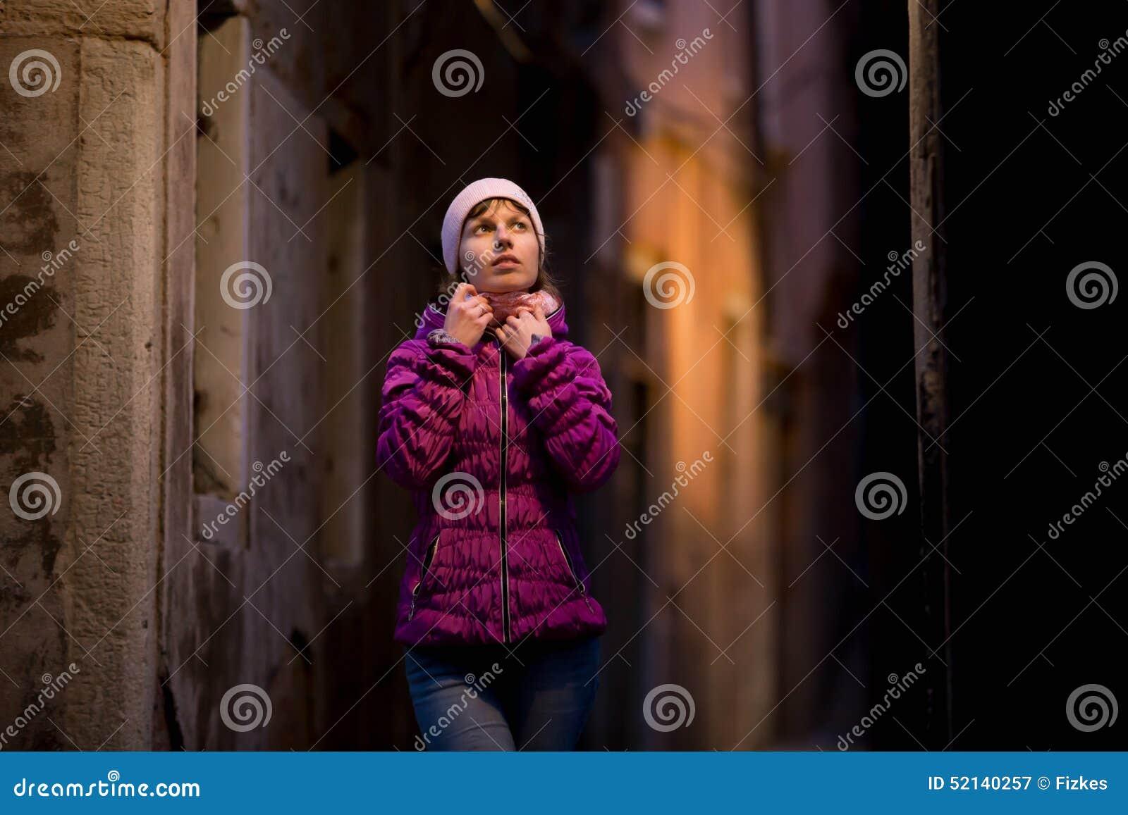 Menina na caminhada na rua na noite