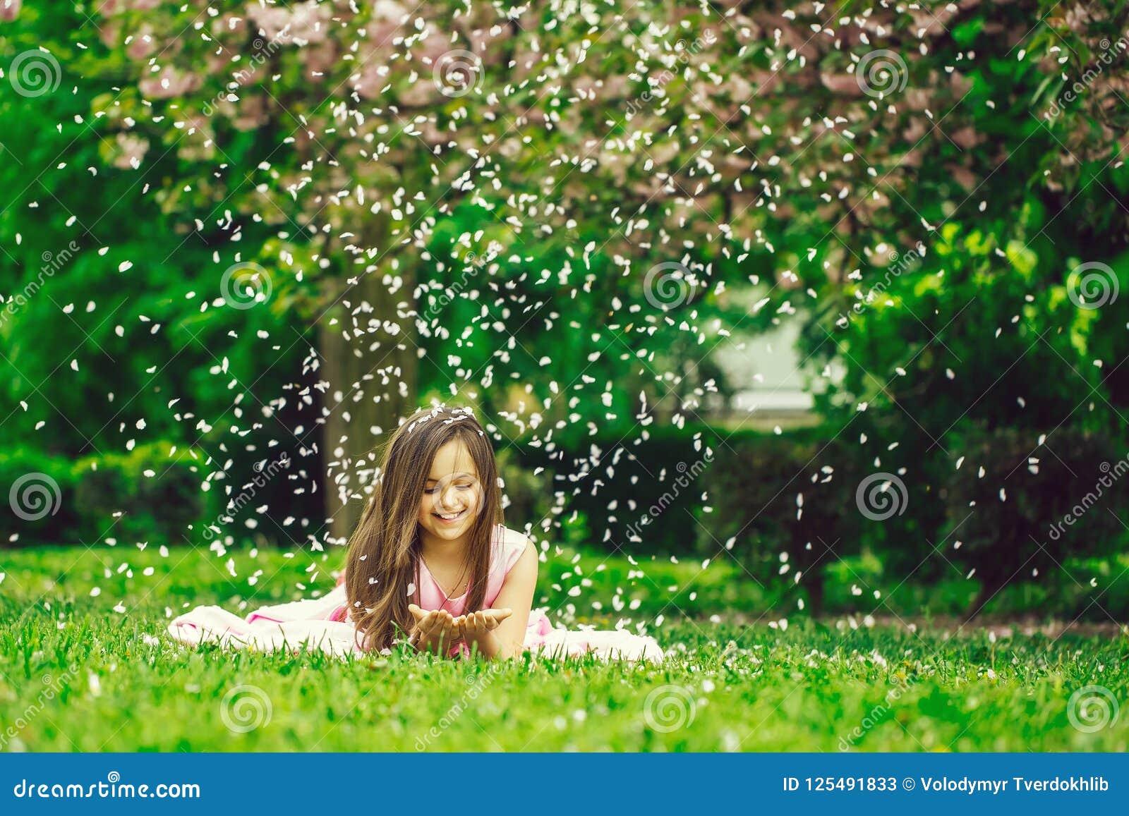 Menina na grama verde com pétalas