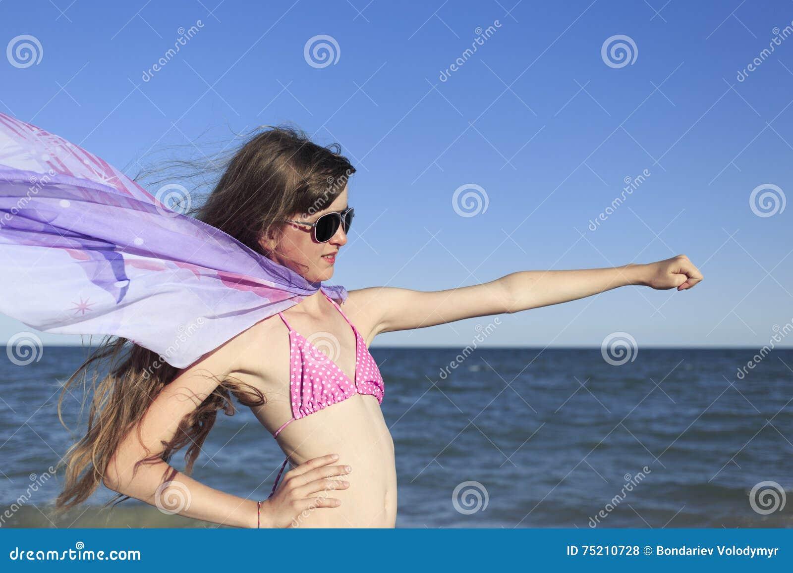 Menina na praia que aprecia um feriado no mar