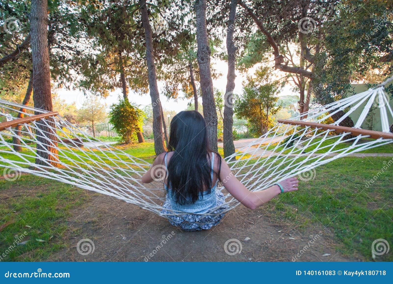 Menina na rede que balança ao admirar a natureza verde