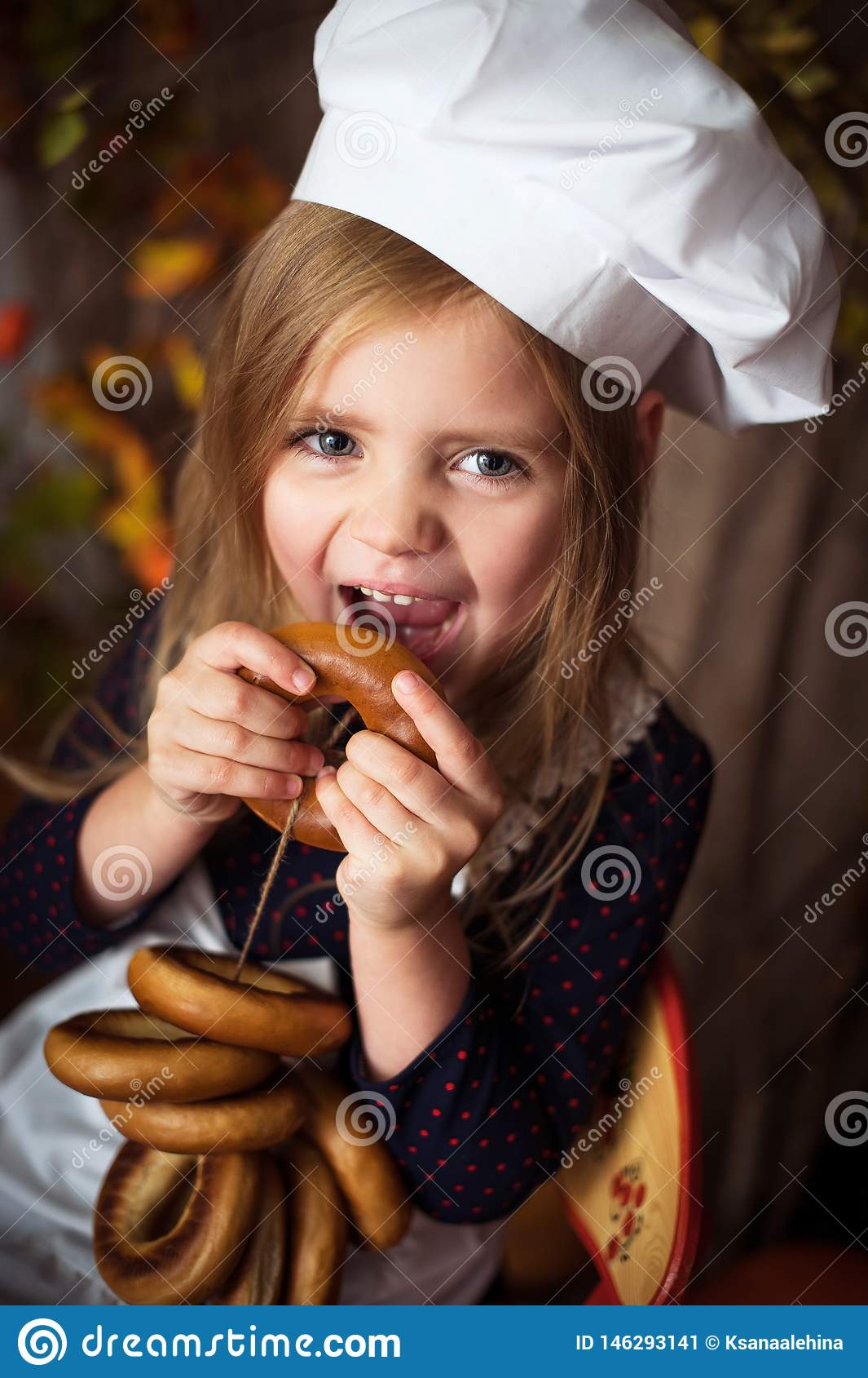 Menina na roupa do cozinheiro com os bagels em no suas m?os e sorriso