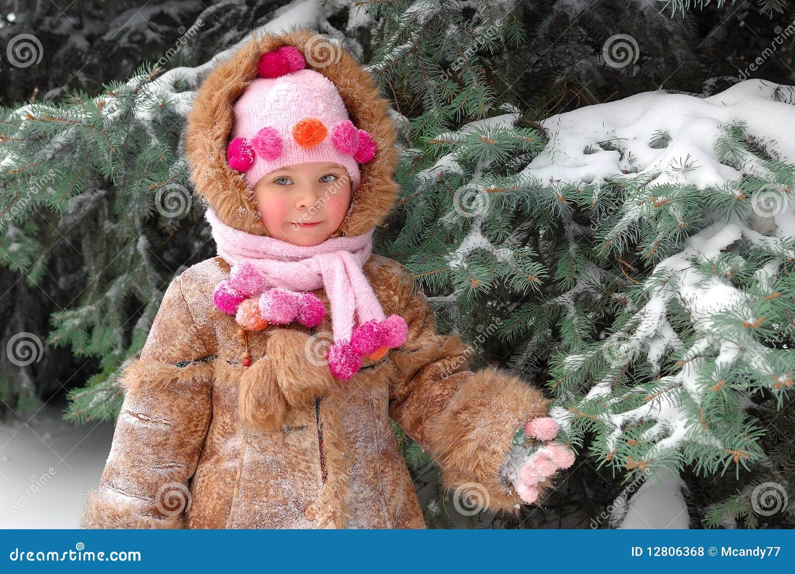 Menina na roupa do inverno em um pinho snow-covered