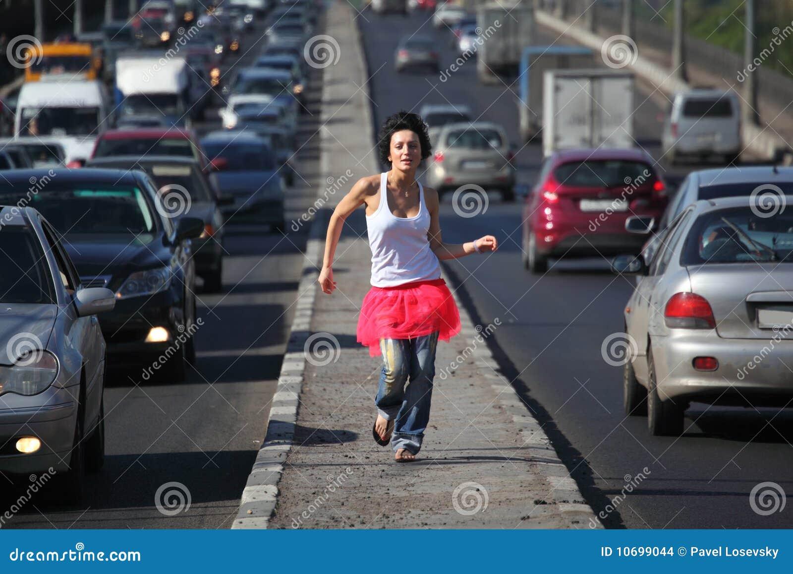 A menina na saia cor-de-rosa funciona no meio da estrada