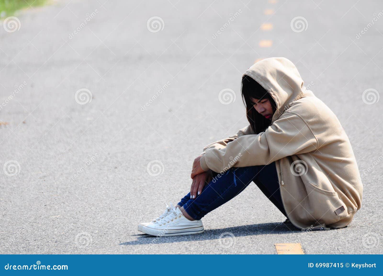 Menina nervosa que senta-se na estrada