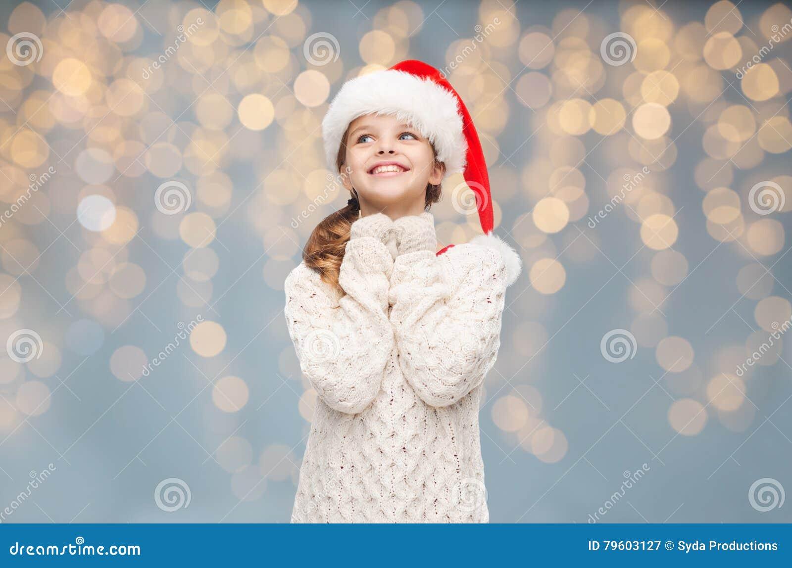 Menina no chapéu de Santa que sonha sobre luzes de Natal
