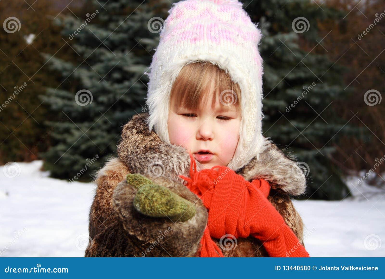Menina no inverno que prende um floco de neve