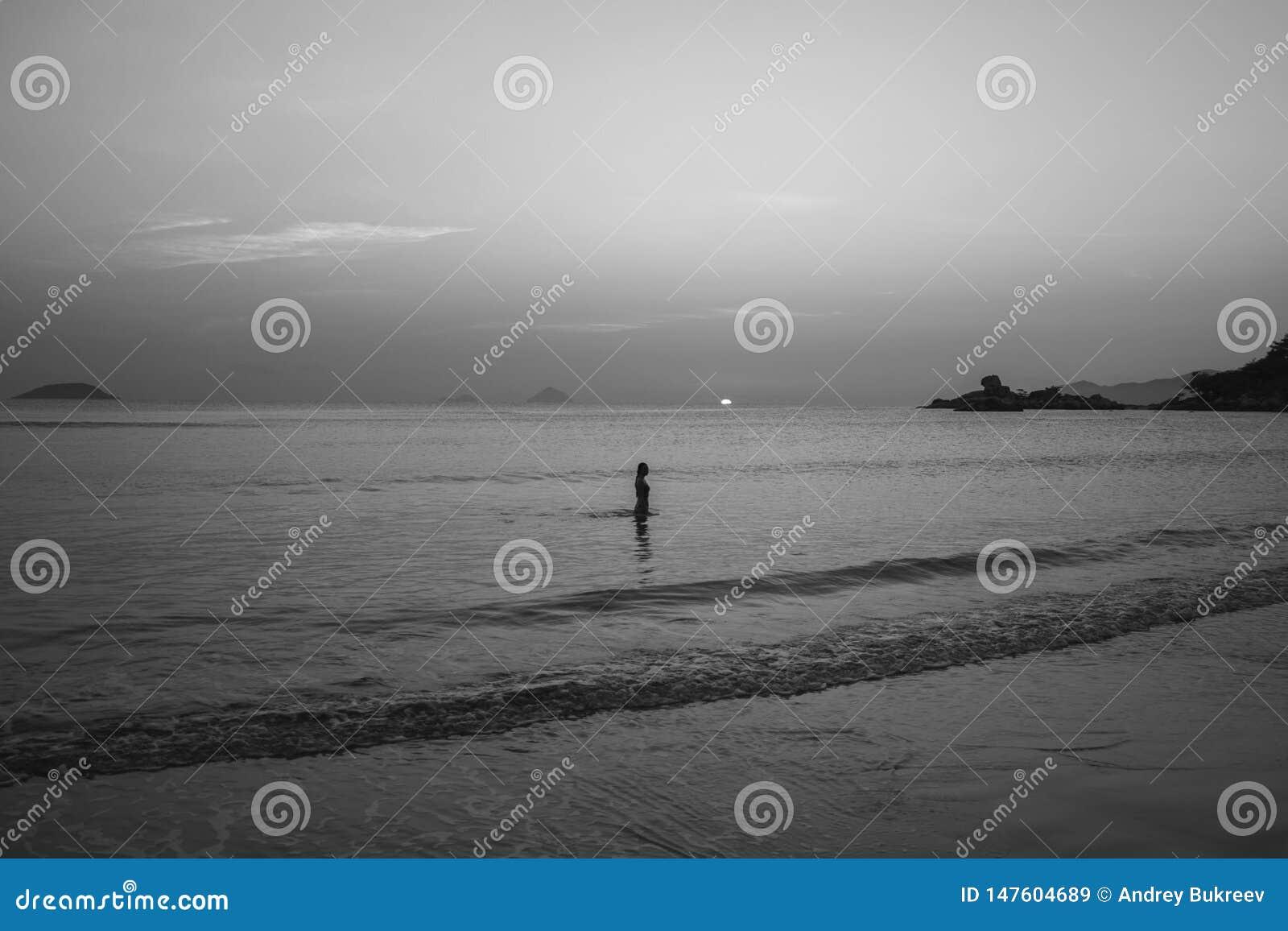 Menina no litoral no fundo do nascer do sol e do por do sol