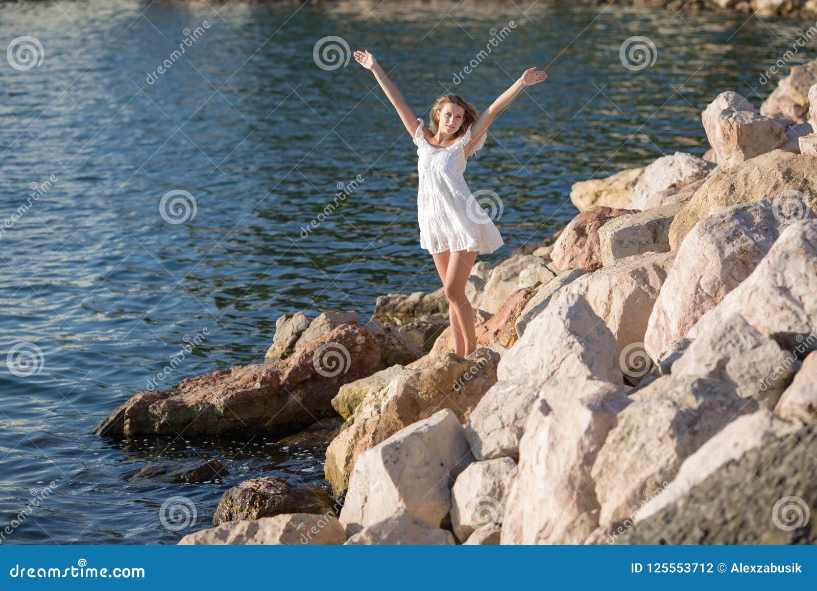 Menina no litoral rochoso no dia ensolarado
