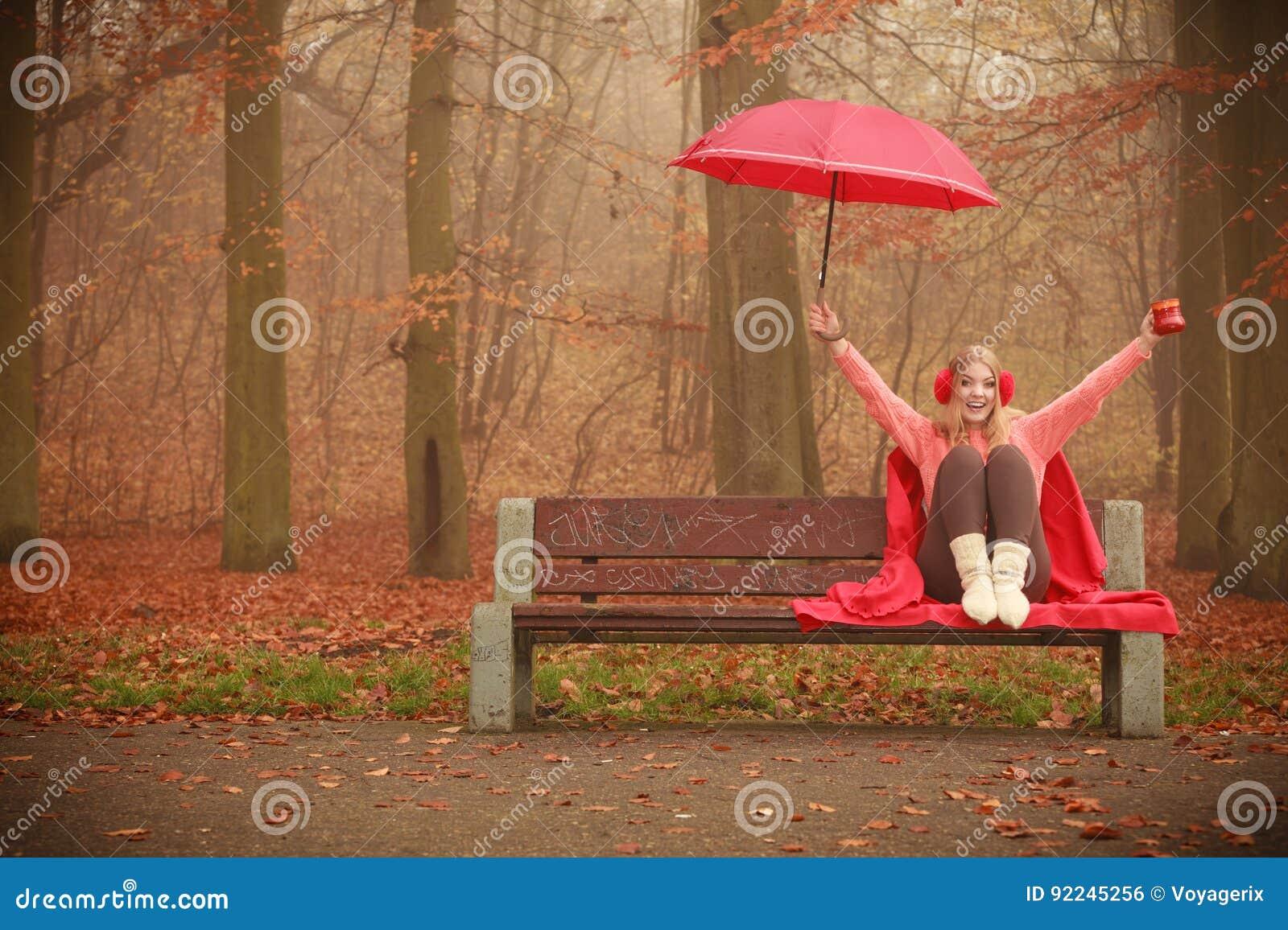 Menina no parque do outono que aprecia a bebida quente