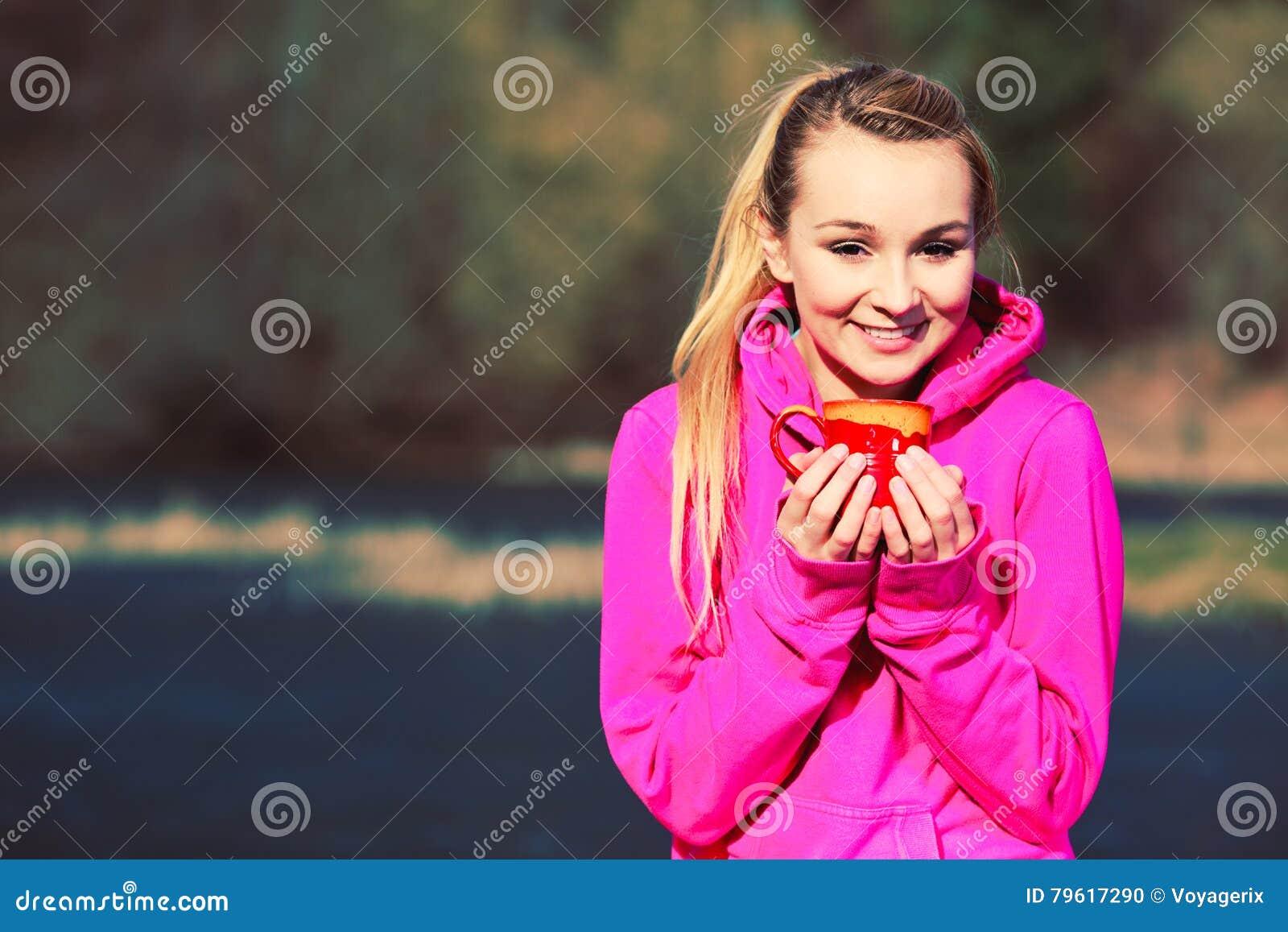 Menina no parque que guarda a caneca