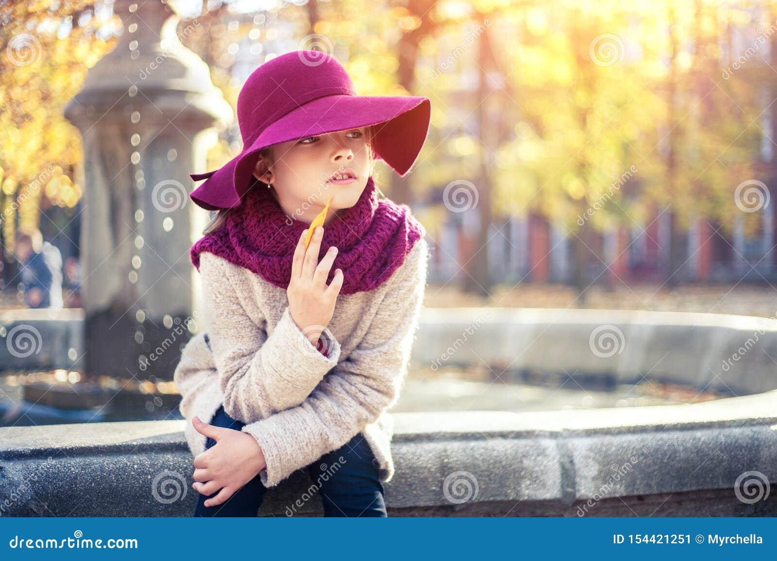 Menina no revestimento e no chapéu clássicos no parque do outono perto da fonte Estação do outono, forma, infância