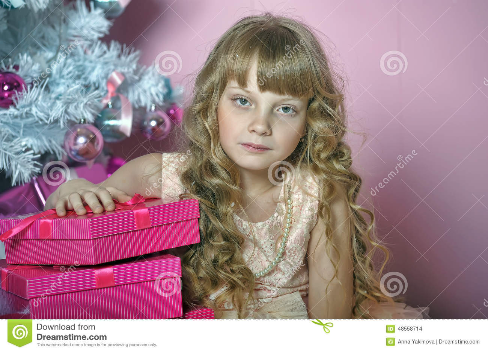 Menina no rosa na árvore de Natal