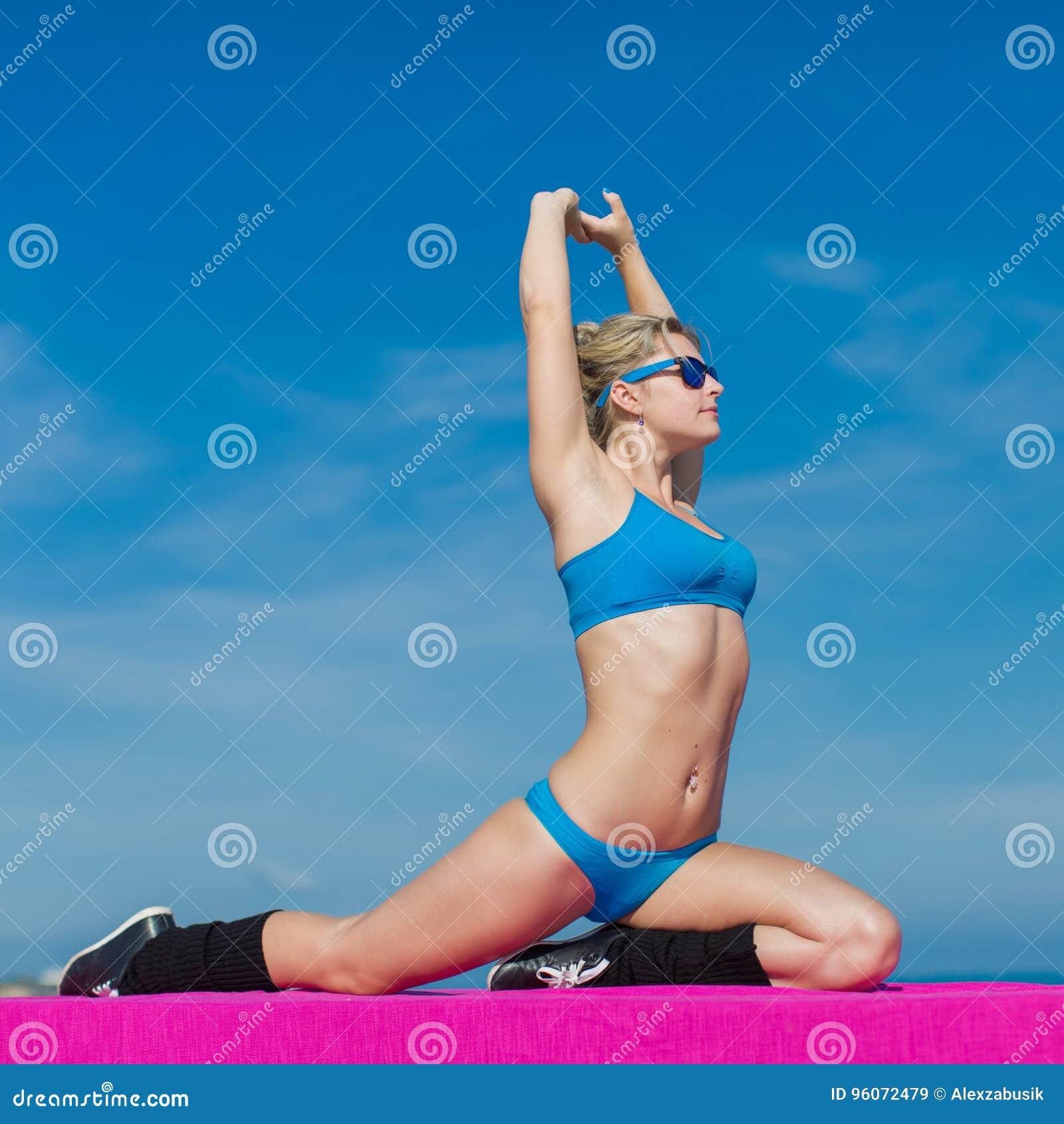 Menina no sportswear e em óculos de sol azuis que treina no ar livre