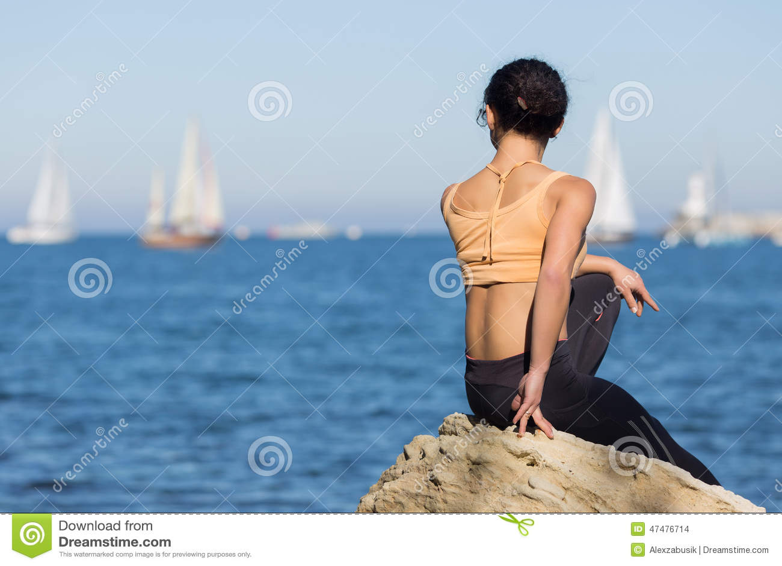 A menina no sportswear observa a regata da vela