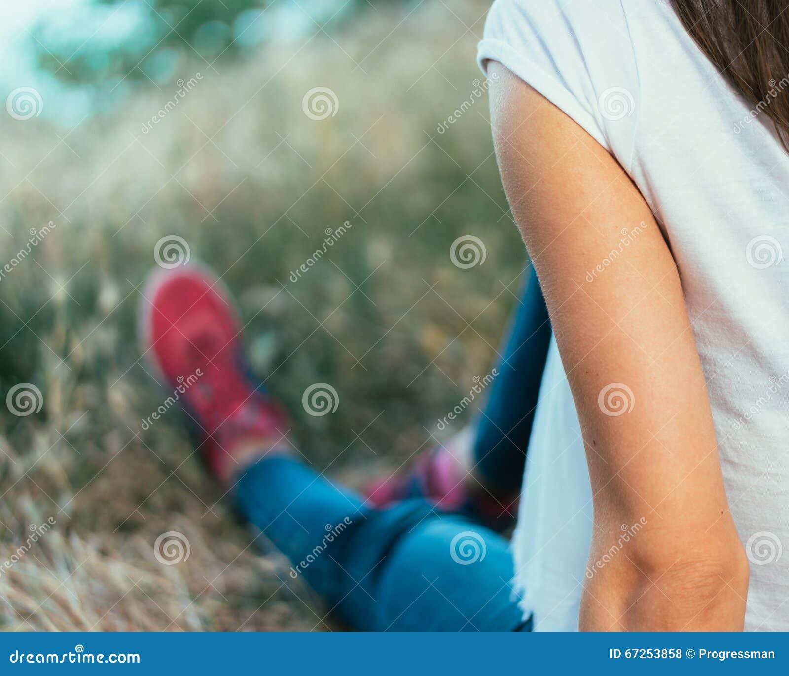 Menina no t-shirt branco, na calças de ganga e nas sapatilhas vermelhas sentando-se no th