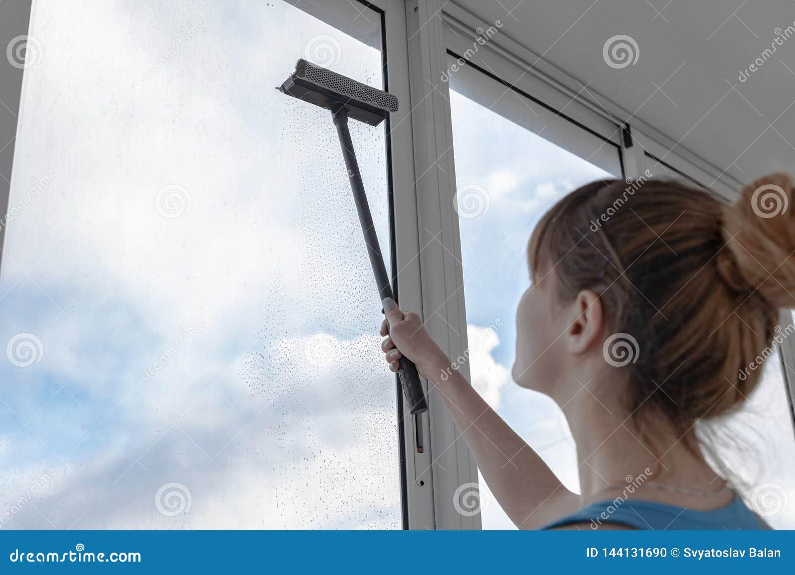 A menina no t-shirt e no short azul de turquesa lava a janela