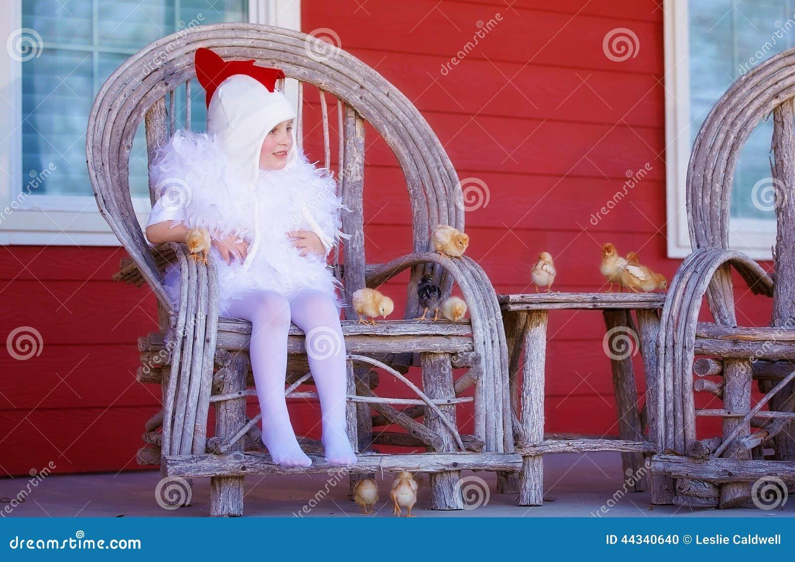 Menina no traje da galinha da mãe com pintainhos do bebê