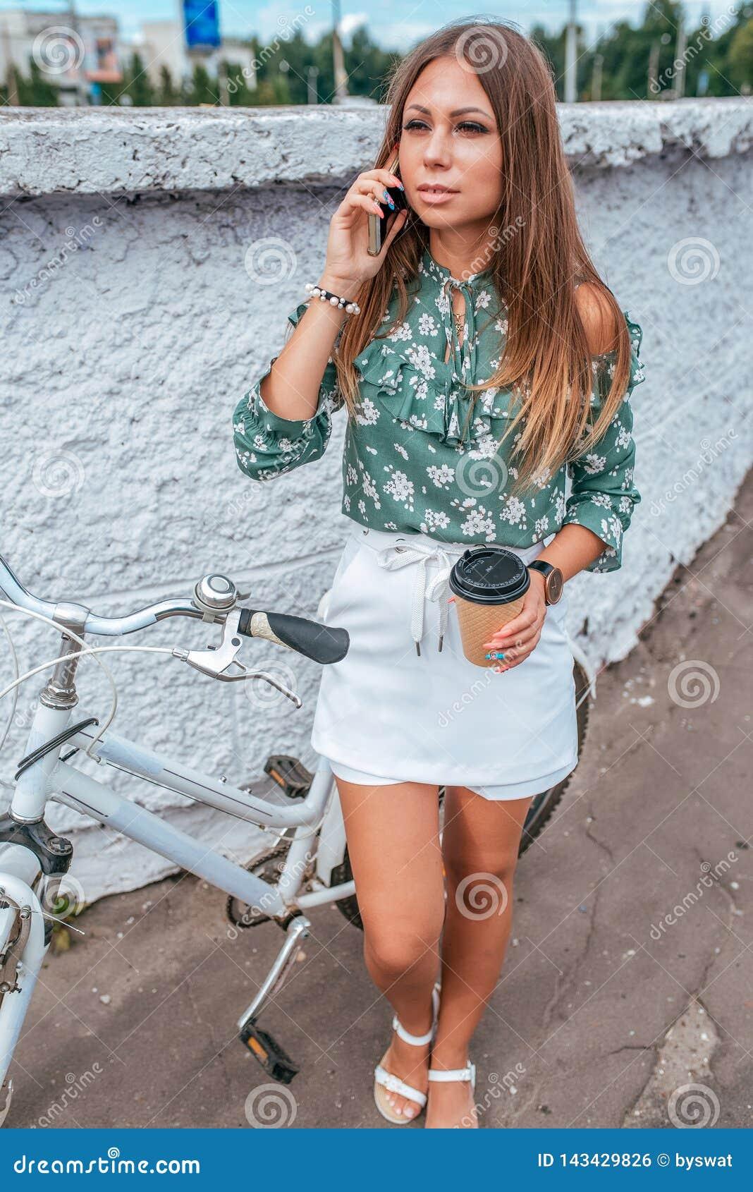 A menina no verão na cidade, chama o telefone, com uma bicicleta, em sua mão um chá da xícara de café Cabelo longo pele bronzeada