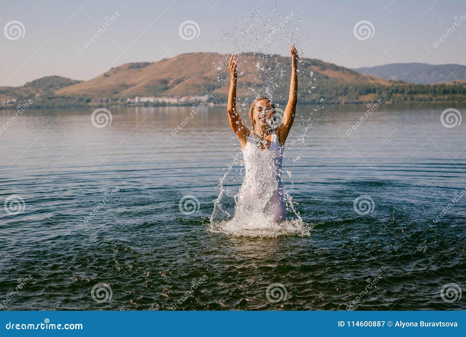 A menina no vestido branco banha-se no verão do lago