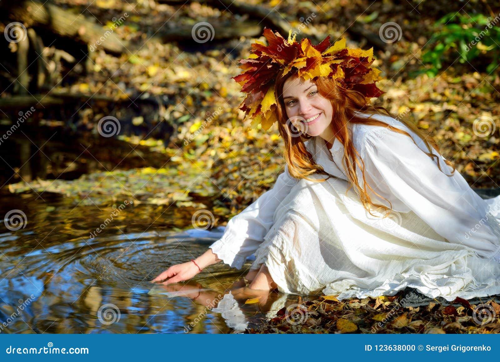 Menina no vestido branco que senta-se e que joga perto da água em uma grinalda das folhas amarelas