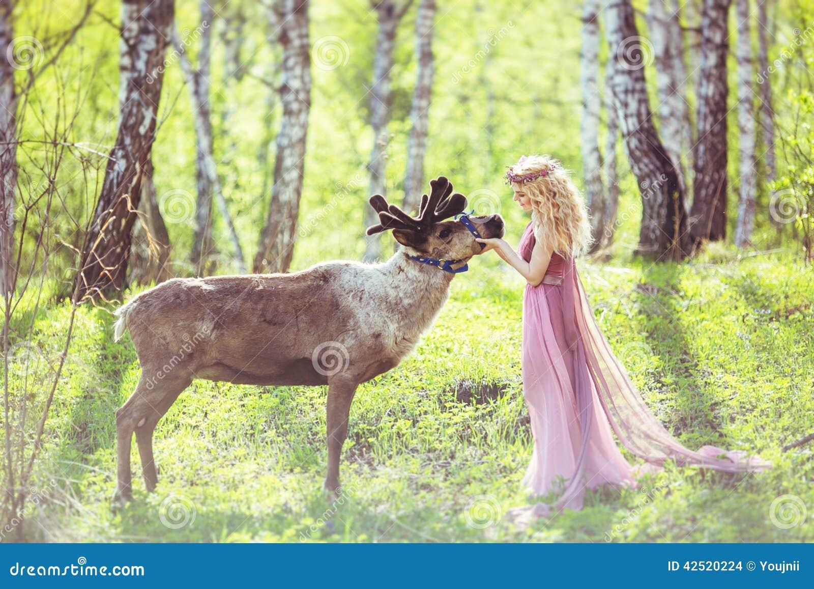 Menina no vestido e na rena feericamente na floresta