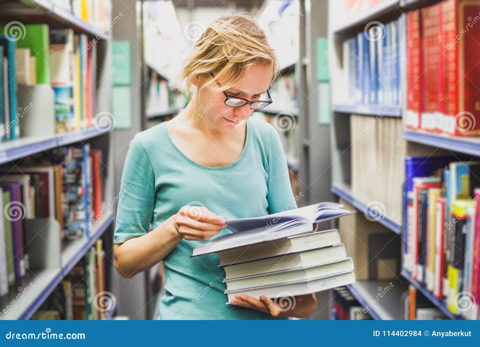 Menina nos livros de leitura da biblioteca, educação do estudante