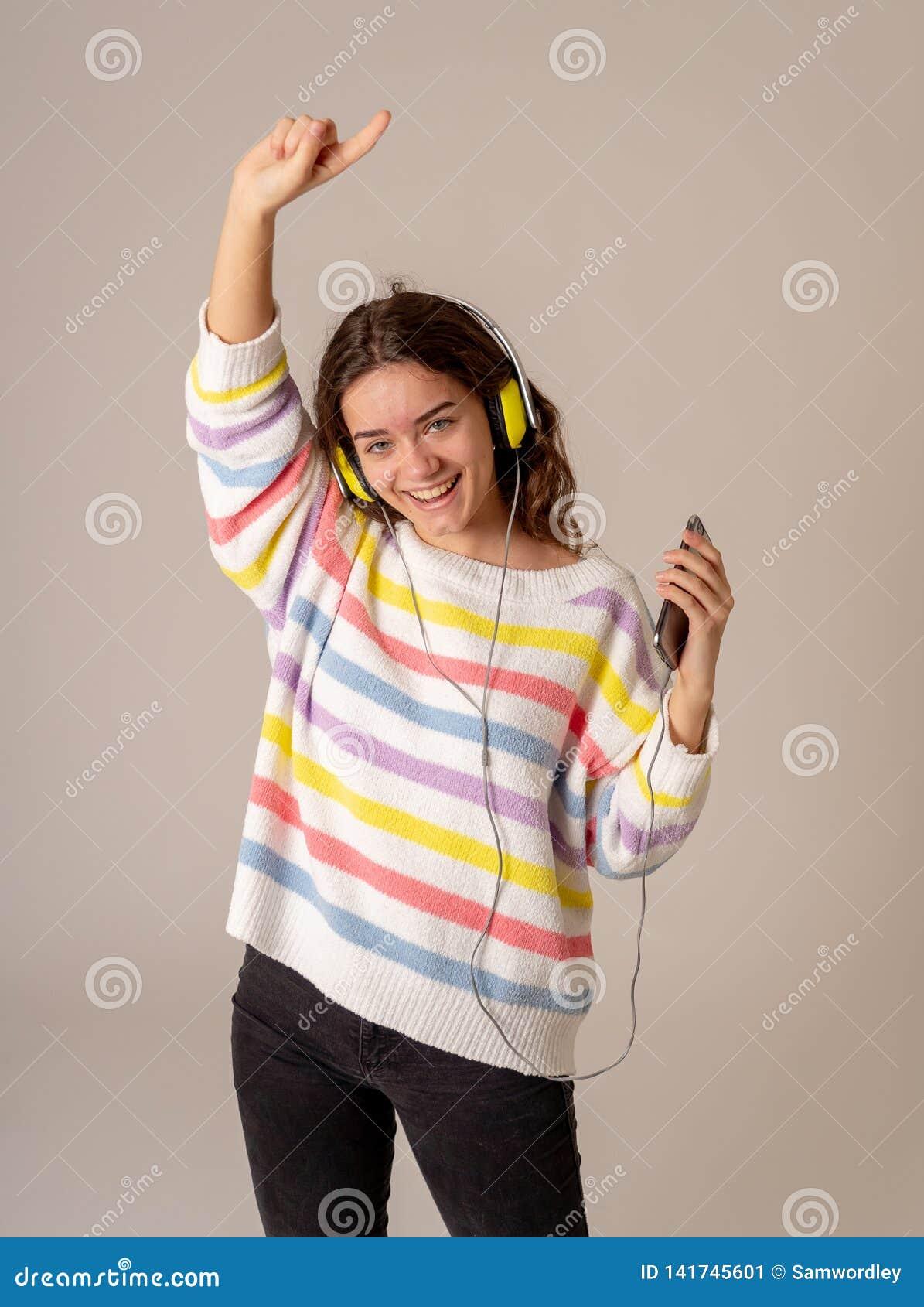 Menina nova bonita do adolescente nos fones de ouvido que escuta a música e a dança isolada no fundo cinzento