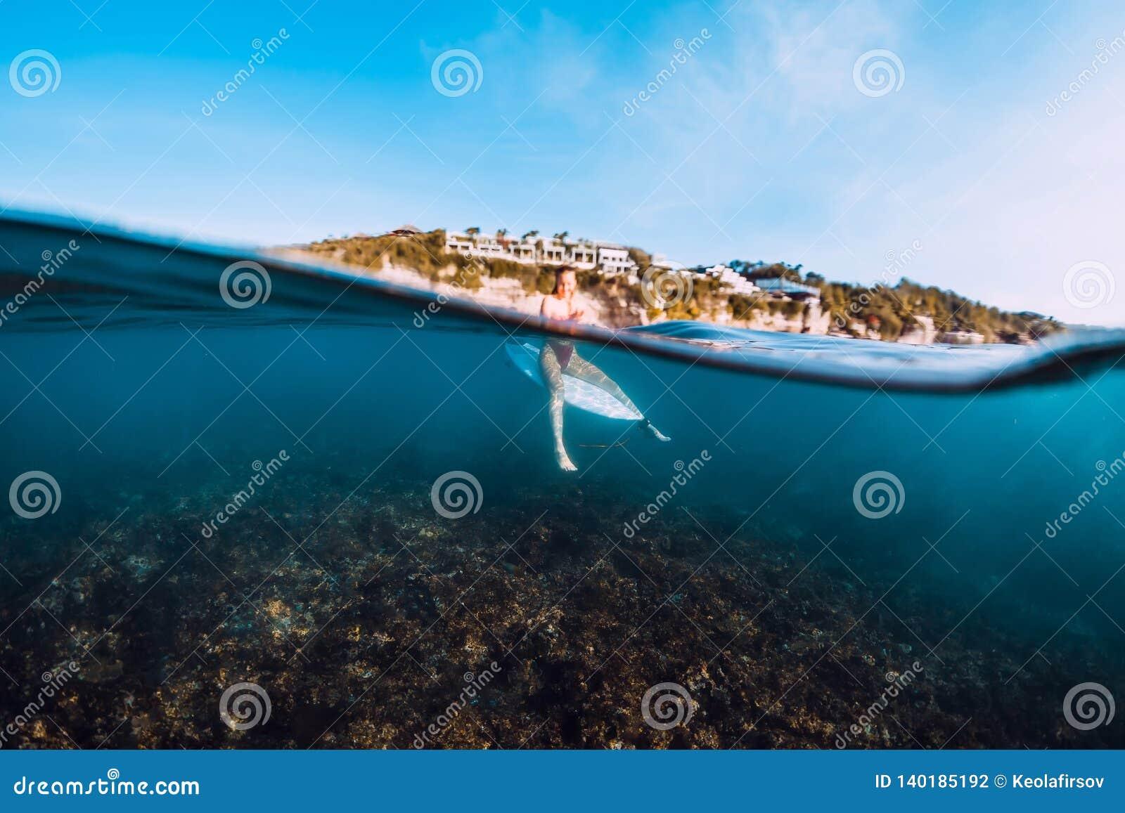 Menina nova da ressaca na prancha subaquática no mar