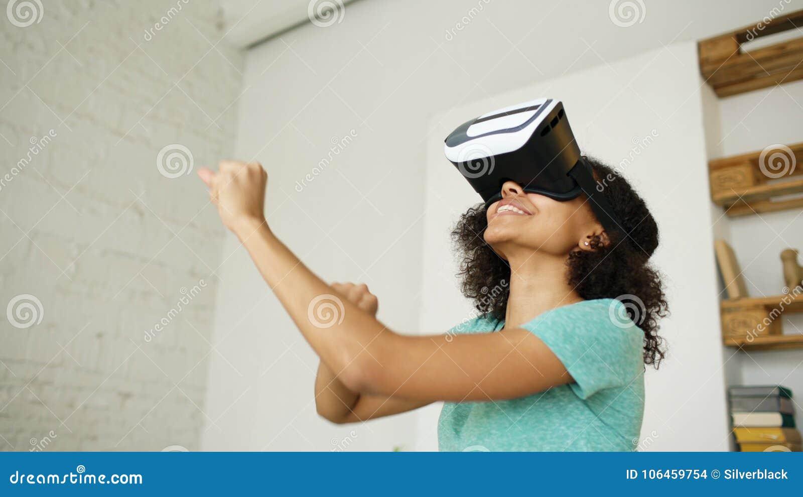 Menina nova de sorriso feliz da raça misturada que obtém a experiência usando vidros dos auriculares de VR da realidade virtual e