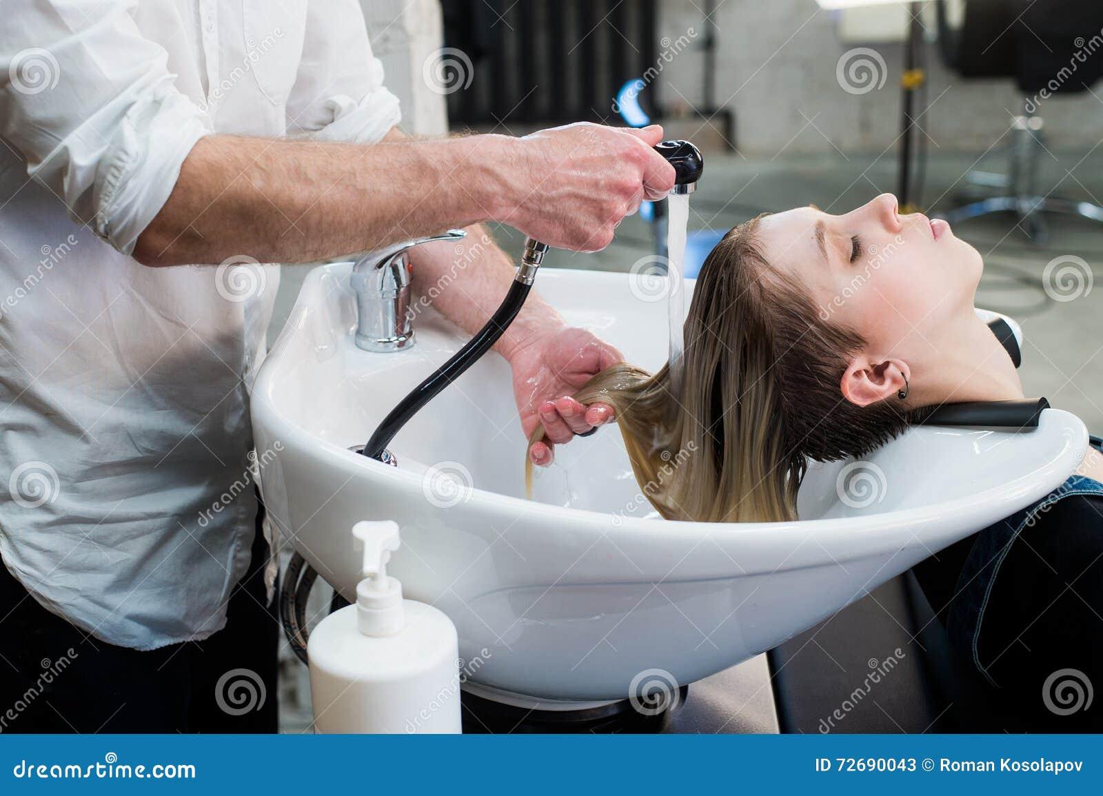 Menina nova do adolescente no cabelo de lavagem do salão de beleza do cabeleireiro pelas mãos do cabeleireiro masculino