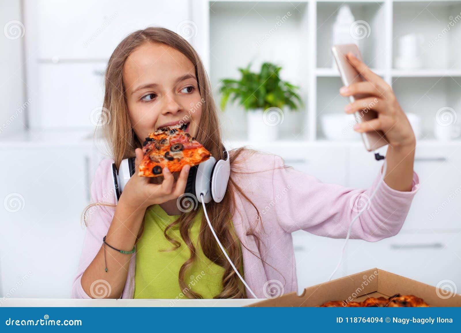 Menina nova do adolescente que come a pizza na cozinha - fazendo um selfi