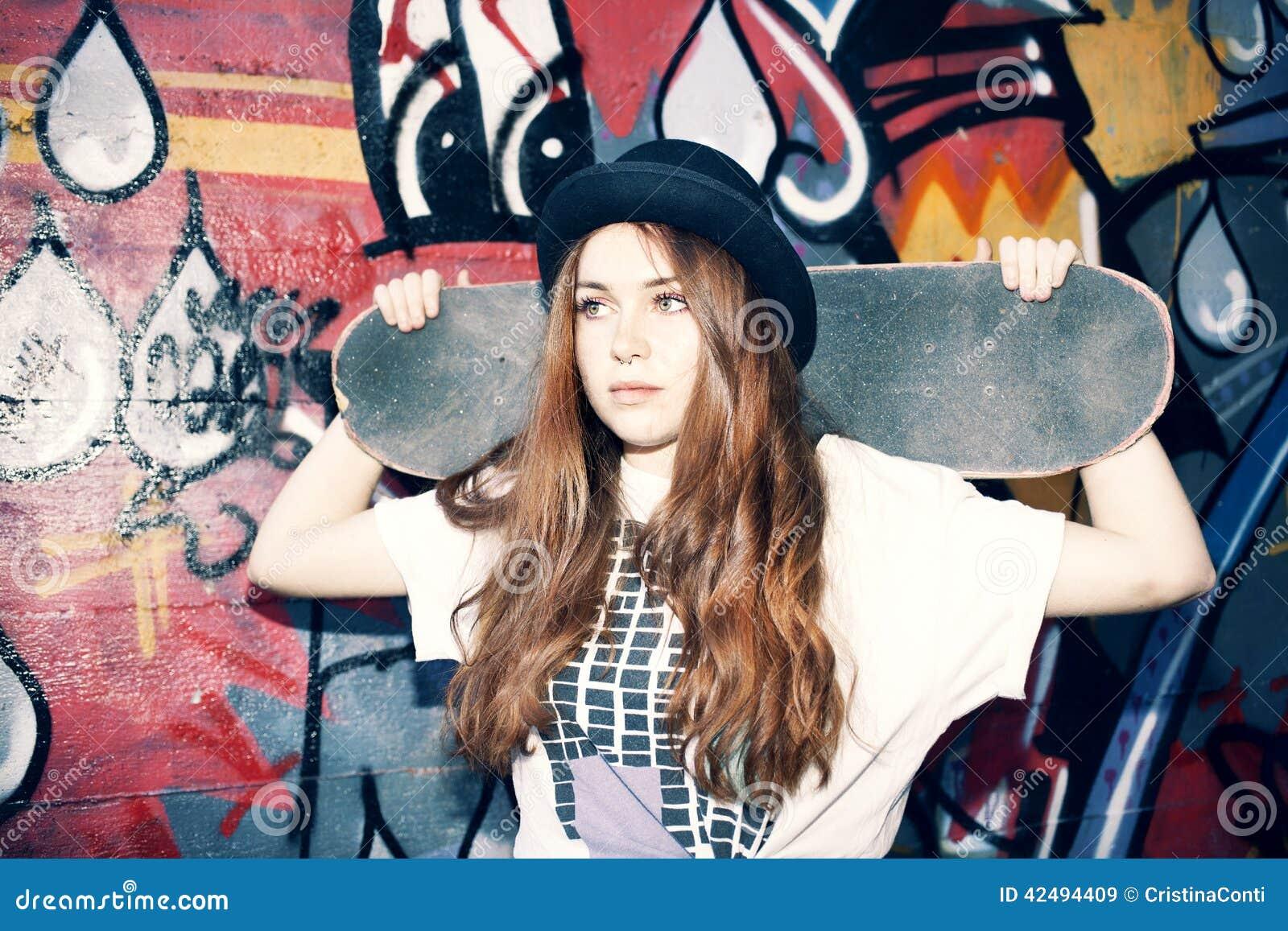 Menina nova do skater que guarda seu patim em um lugar urbano