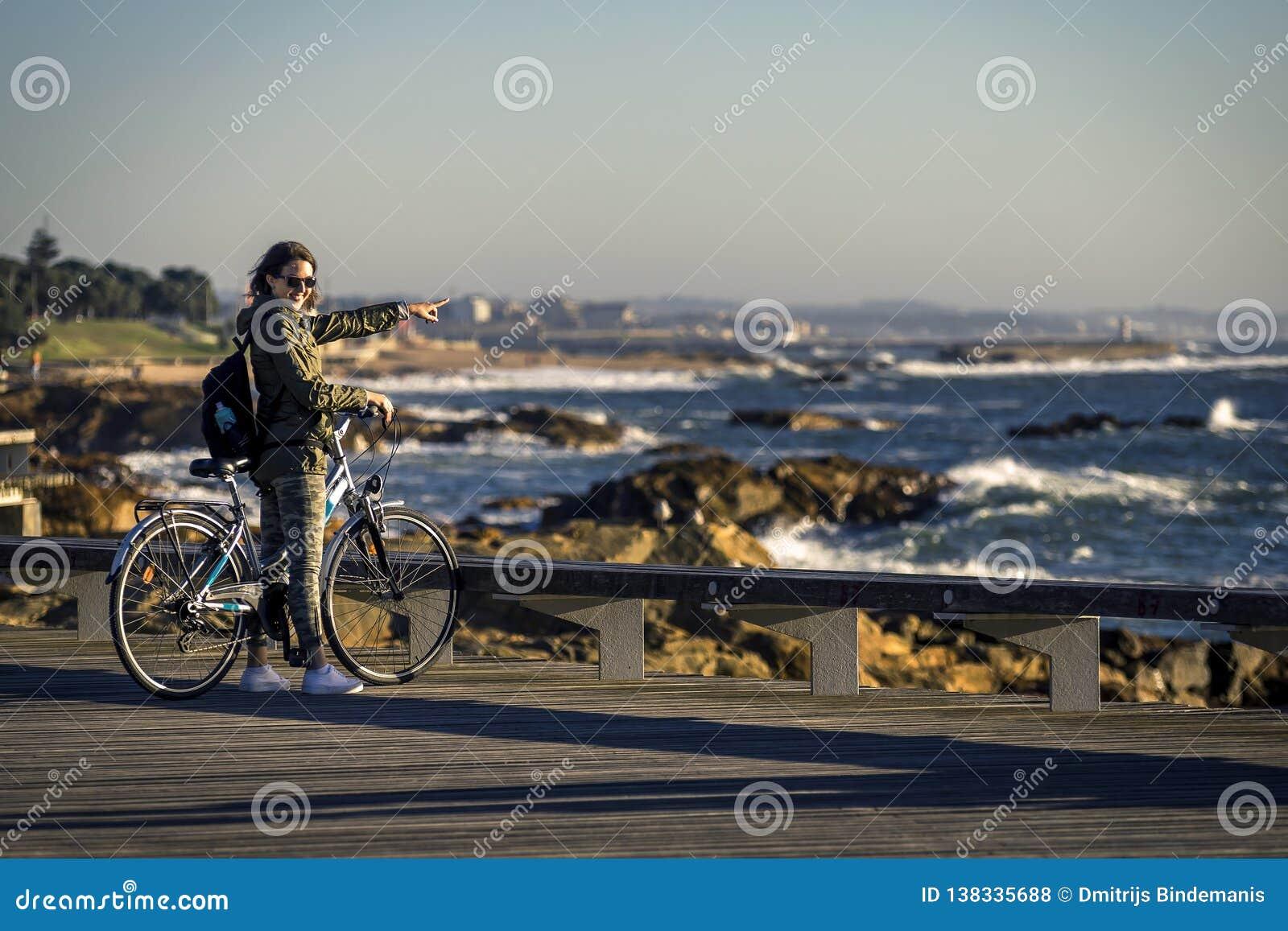 A menina nova e bonita está montando uma bicicleta pelo cais ao lado do Oceano Atlântico