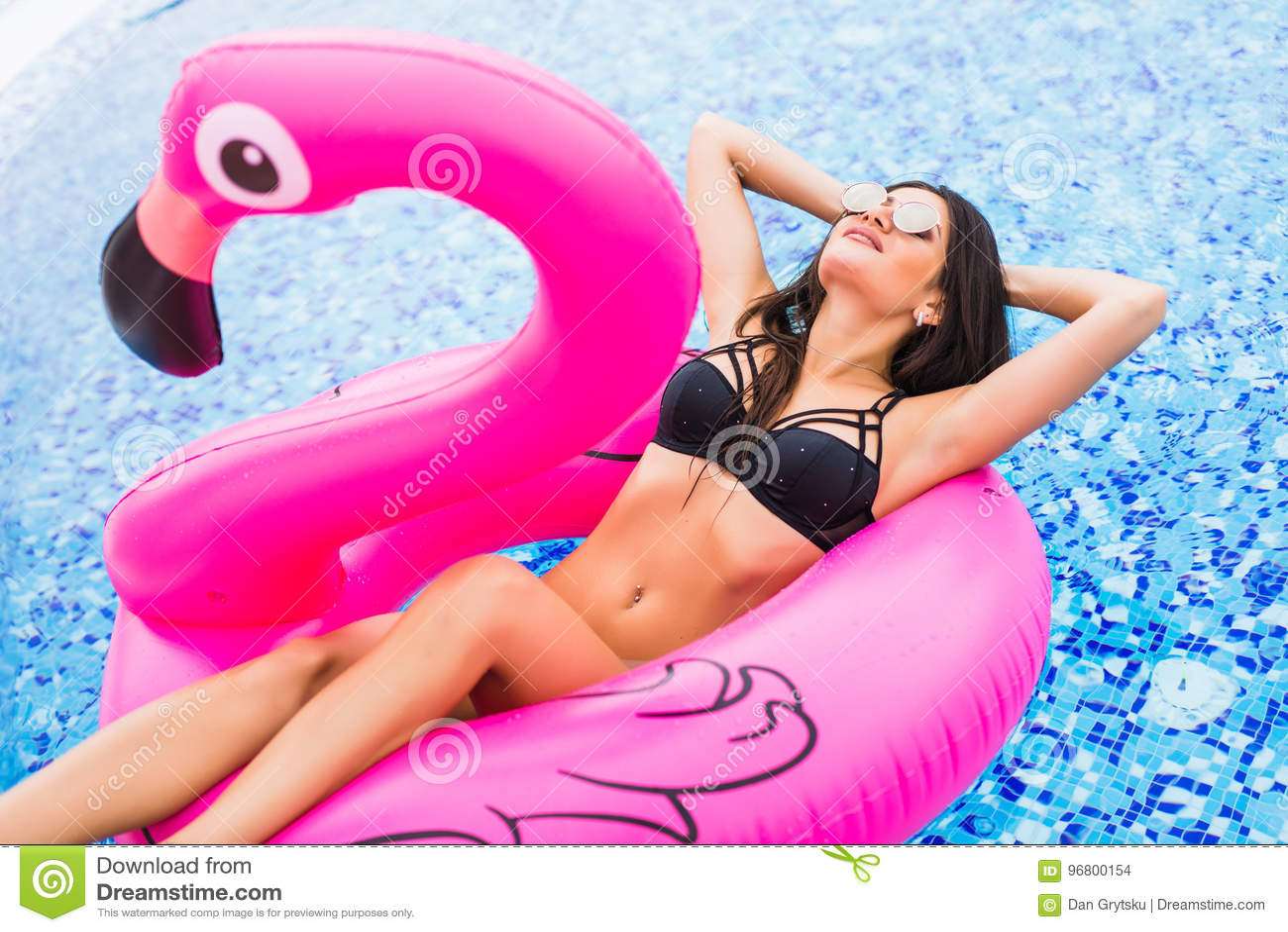 Menina nova e  sexy  que tem o divertimento e que ri em um colchão cor-de-rosa gigante inflável do flutuador da associação do fla