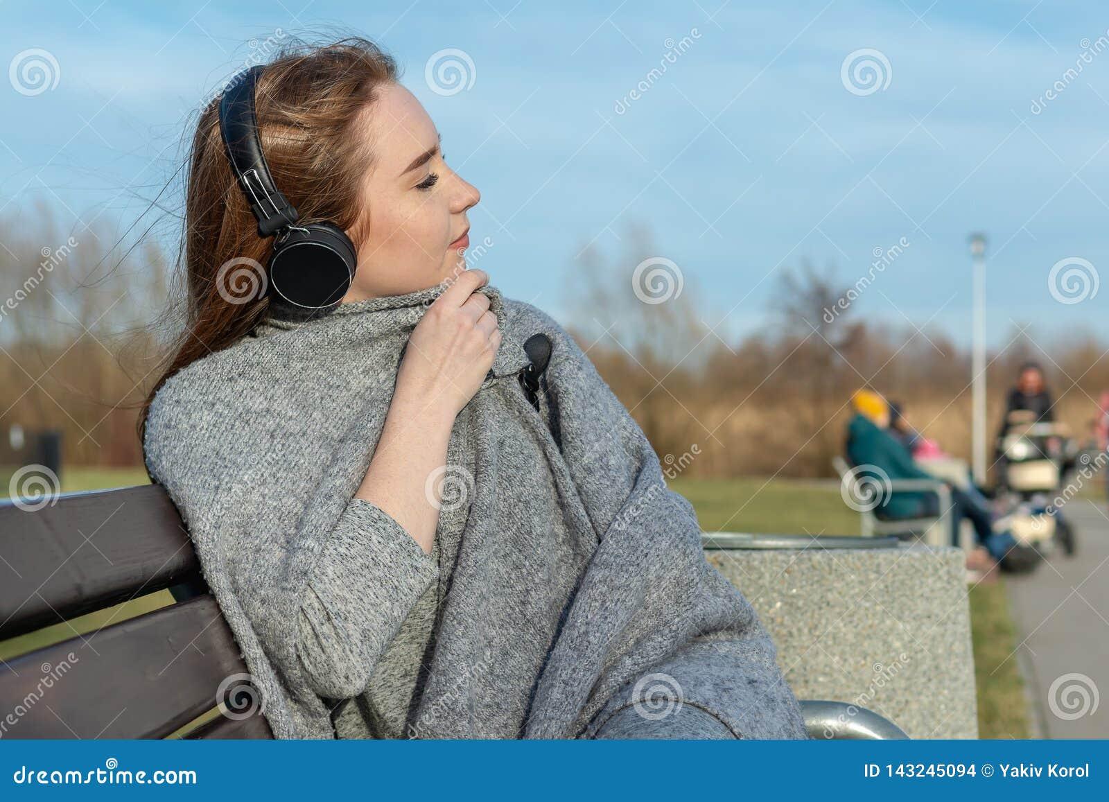 A menina nova, feliz do ruivo na primavera no parque perto do rio escuta a música através dos fones de ouvido sem fio do bluetoot