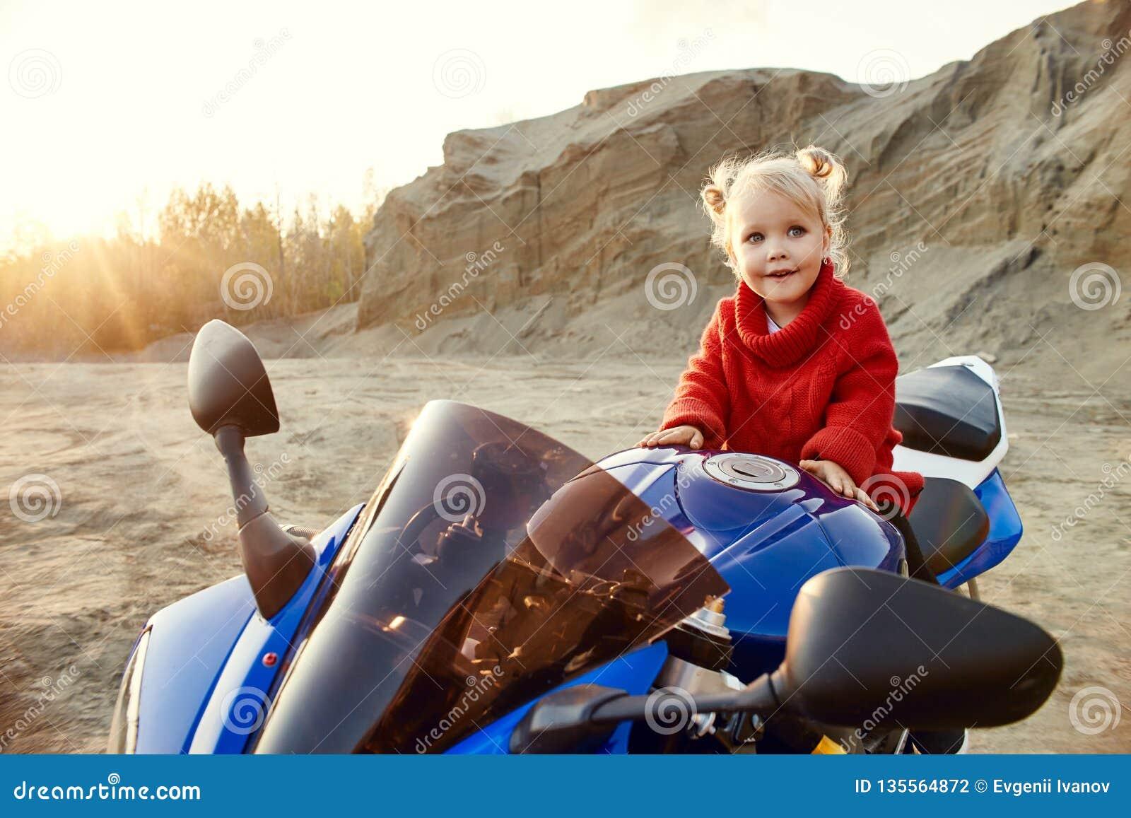 Menina nova que senta-se em uma competência da motocicleta, bonita pouco motociclista em uma bicicleta dos esportes na natureza A