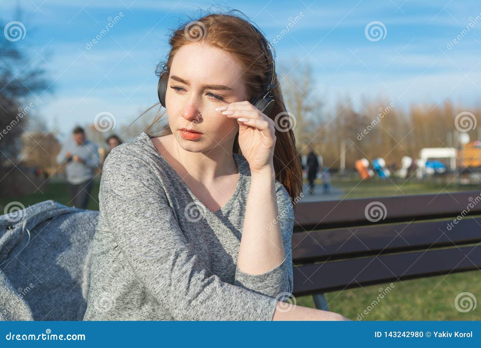 A menina nova, triste do ruivo do grito na primavera no parque perto do rio escuta a música através dos fones de ouvido sem fio d